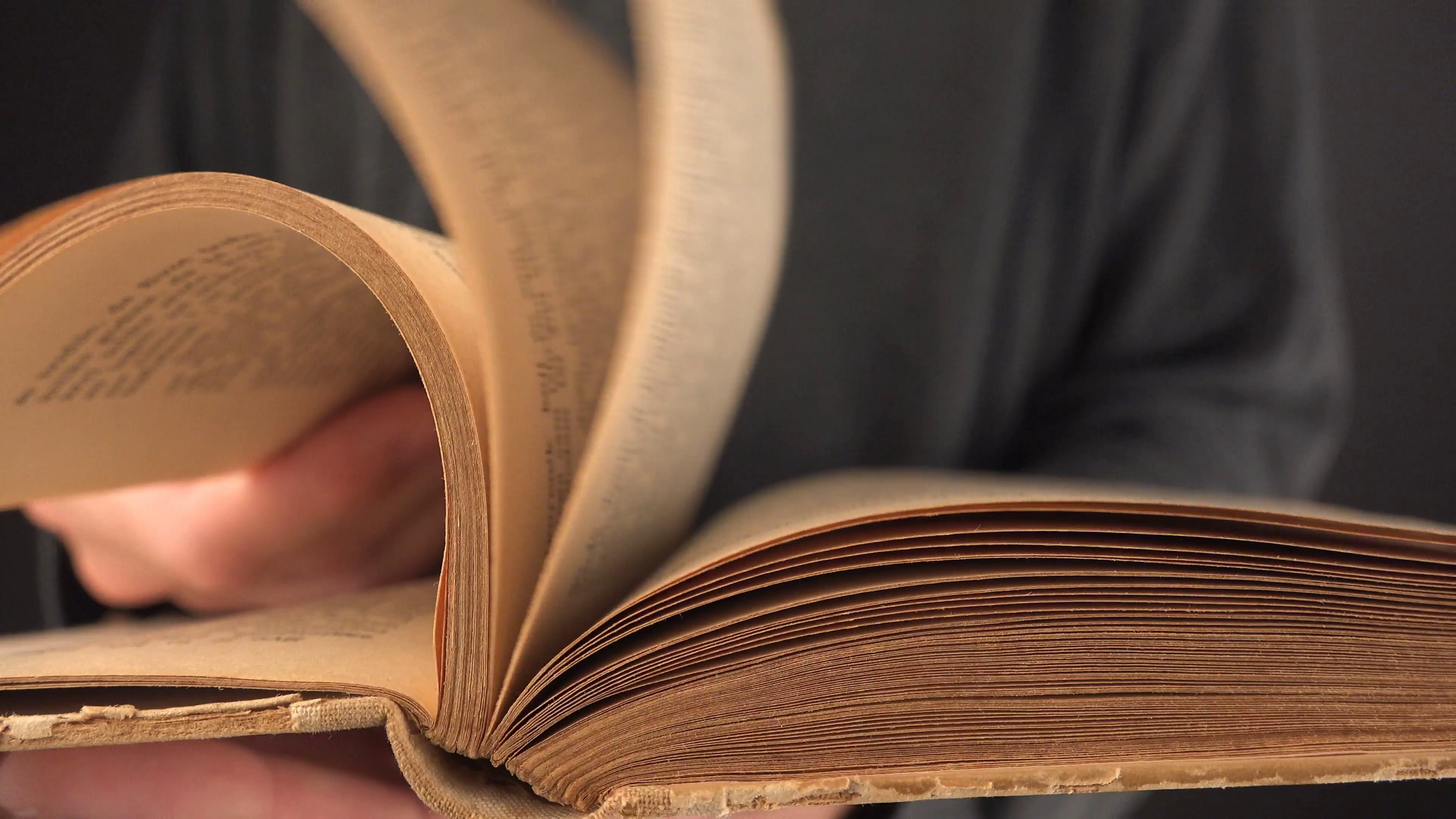 Man turning yellow pages of old vintage book in search for text and ...
