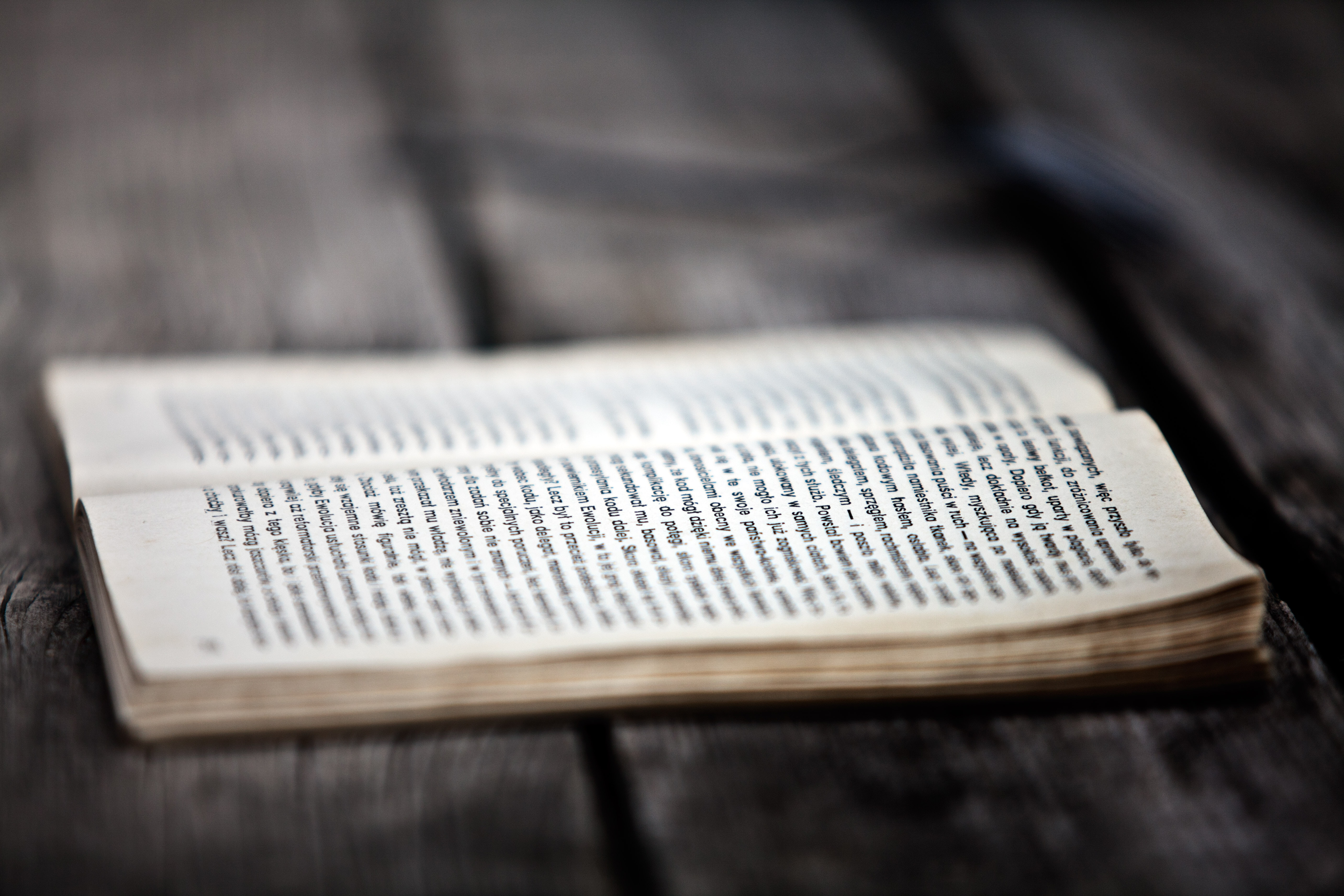Opened book on wooden board photo