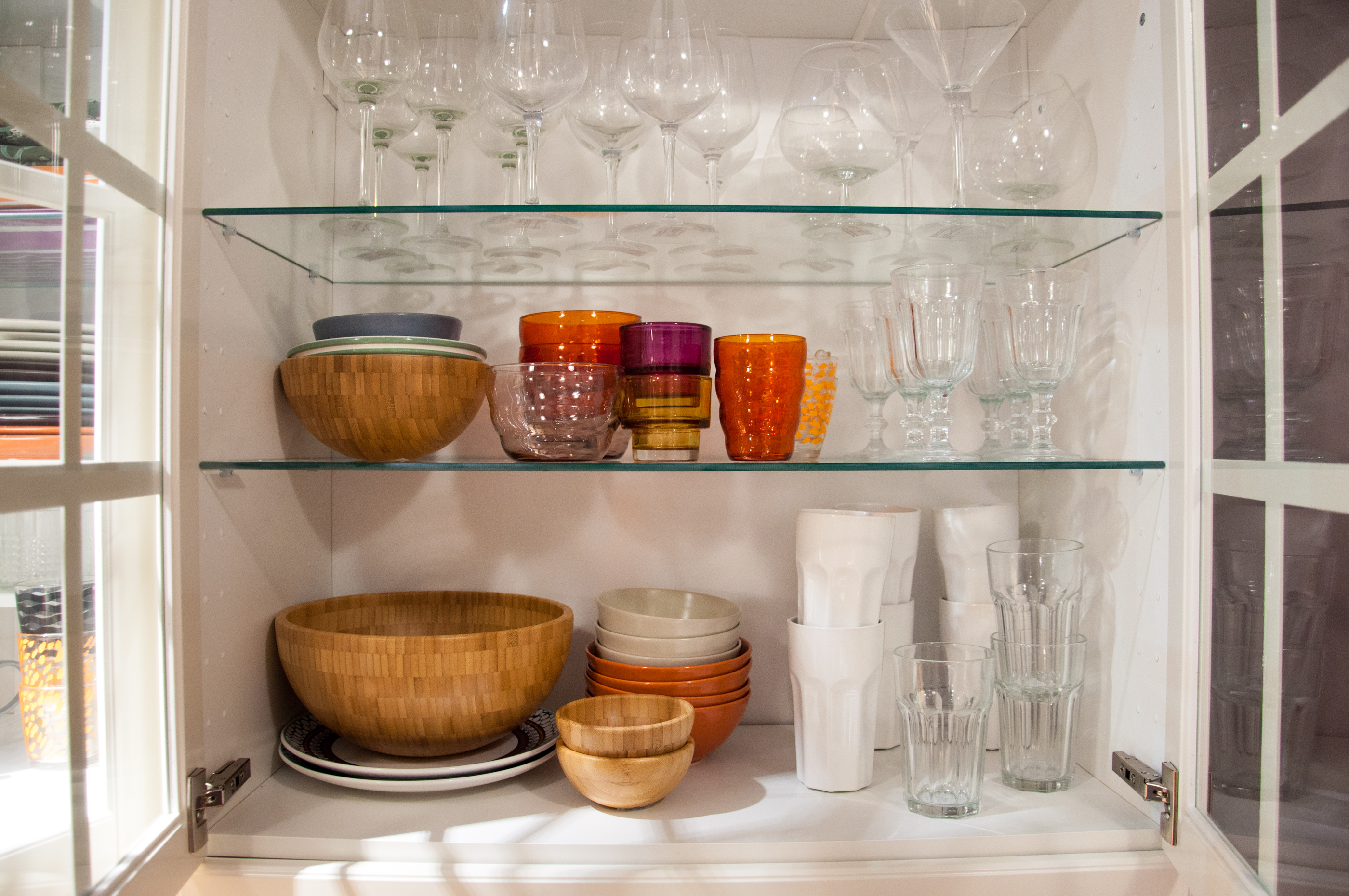 Opened cupboard with kitchenware inside photo
