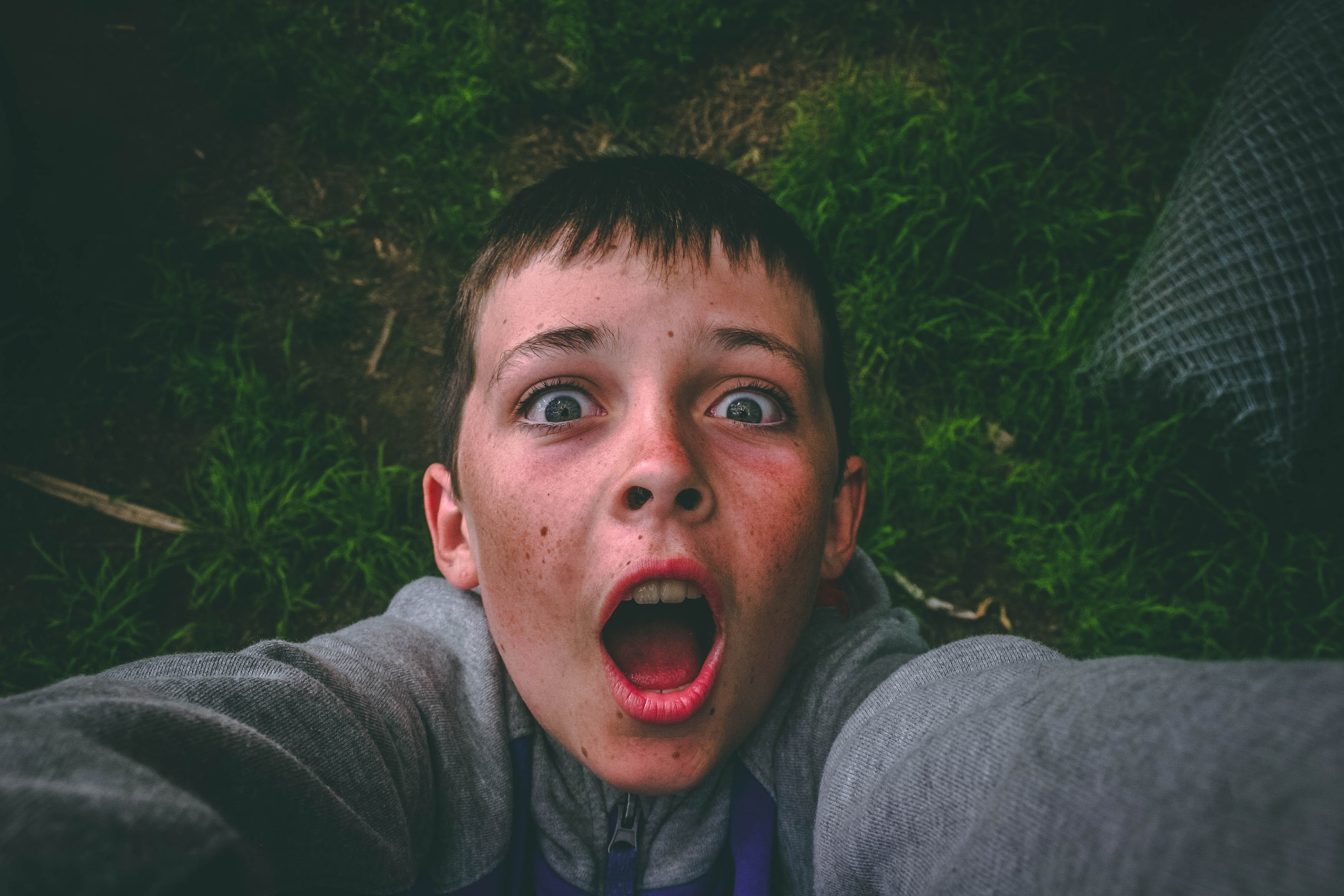 Opened mouth black haired boy in gray full-zip jacket standing on grass field taking selfie photo