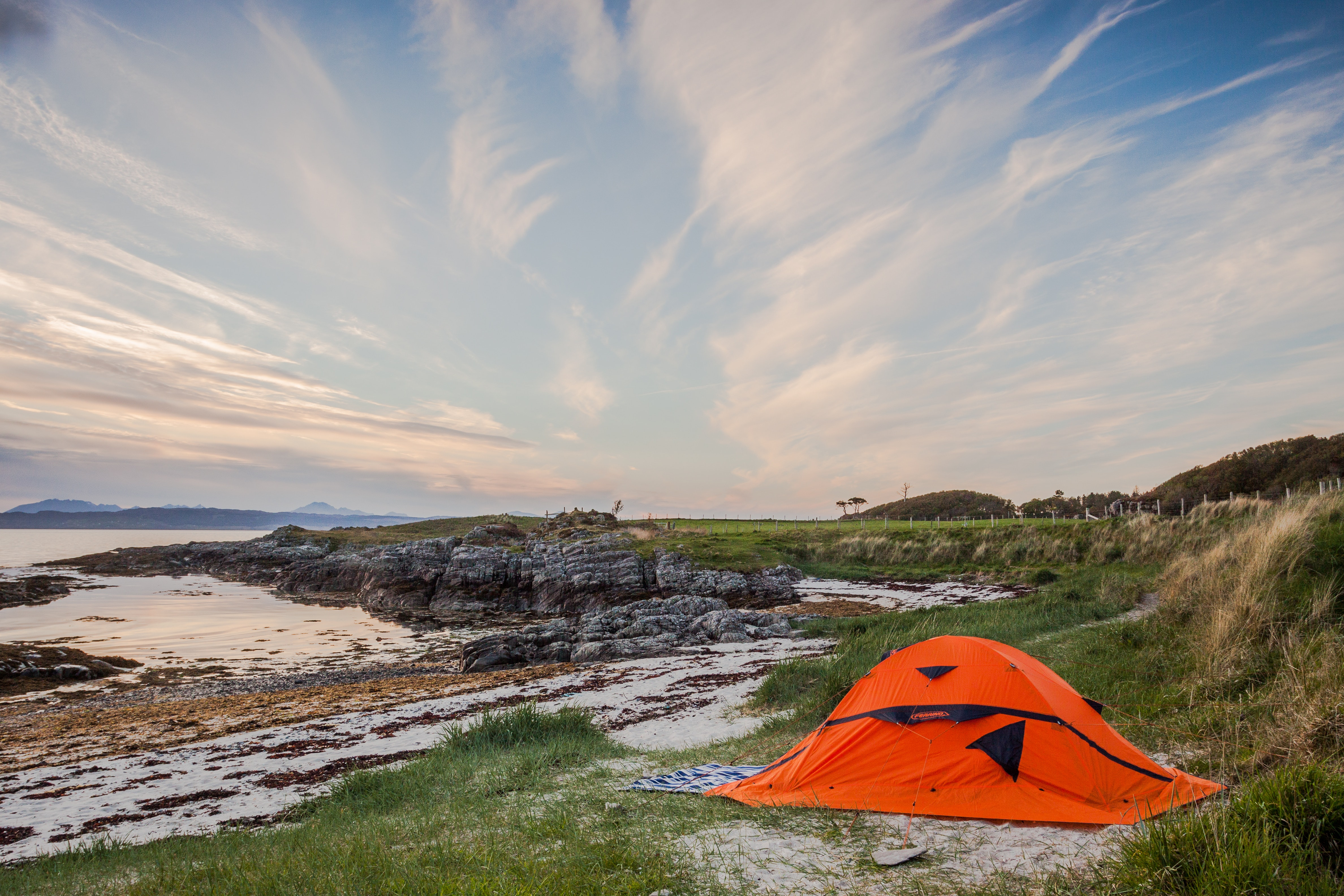 Orange camping tent near body of water during daytime photo