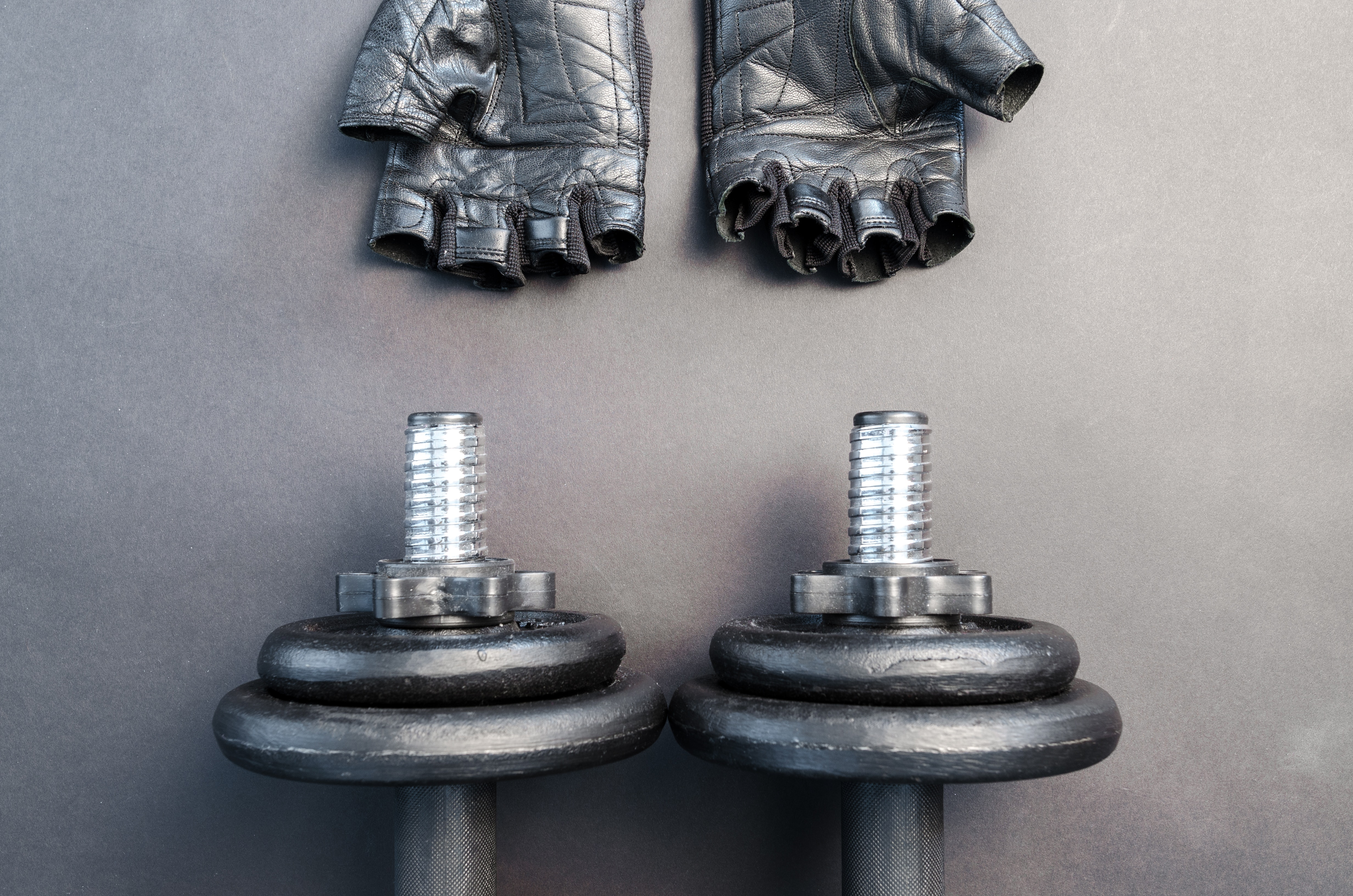 Pair of fingerless gloves and adjustable dumbbells photo