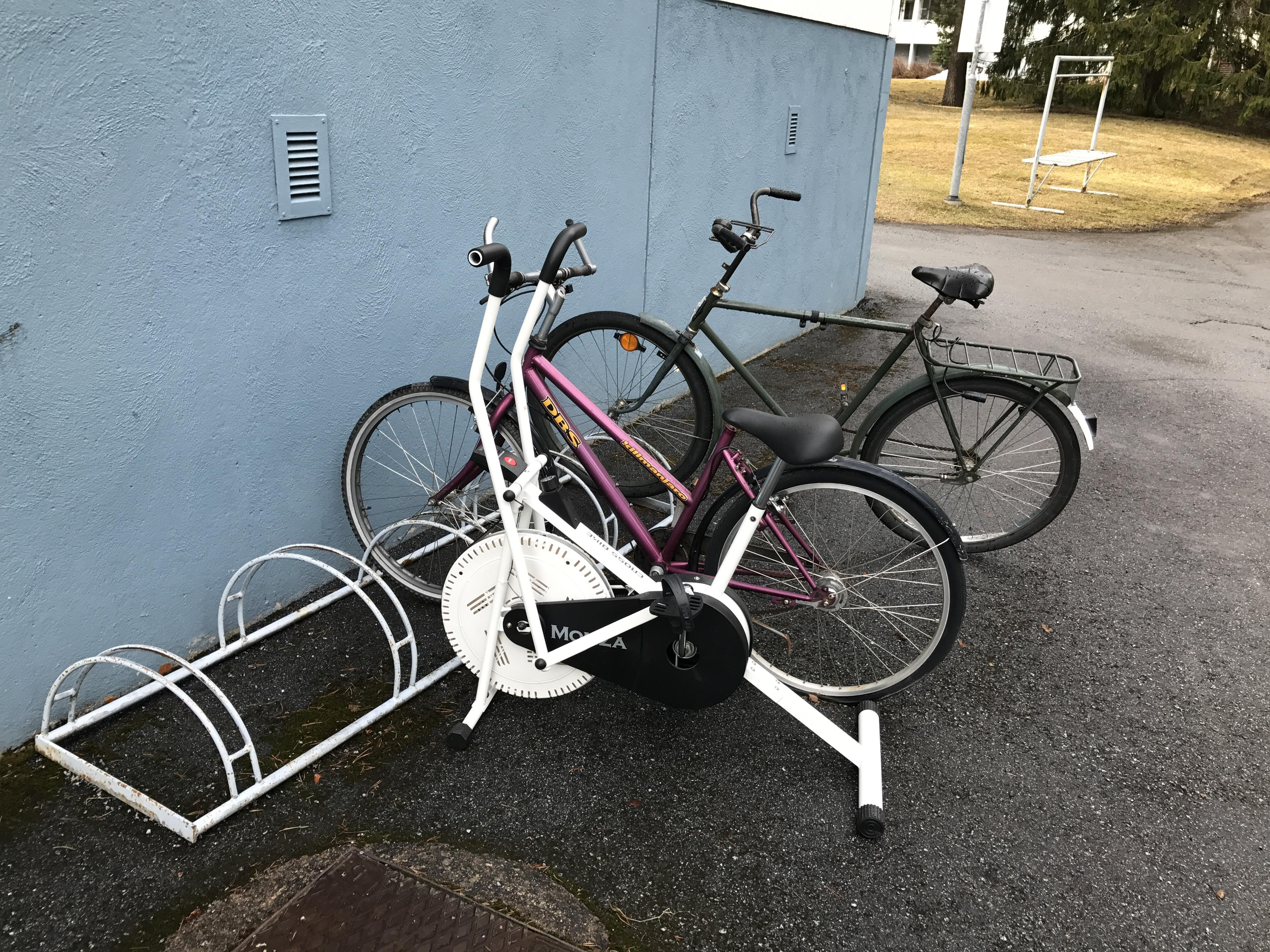 An exercise bike parked in a bike rack. : mildlyinteresting