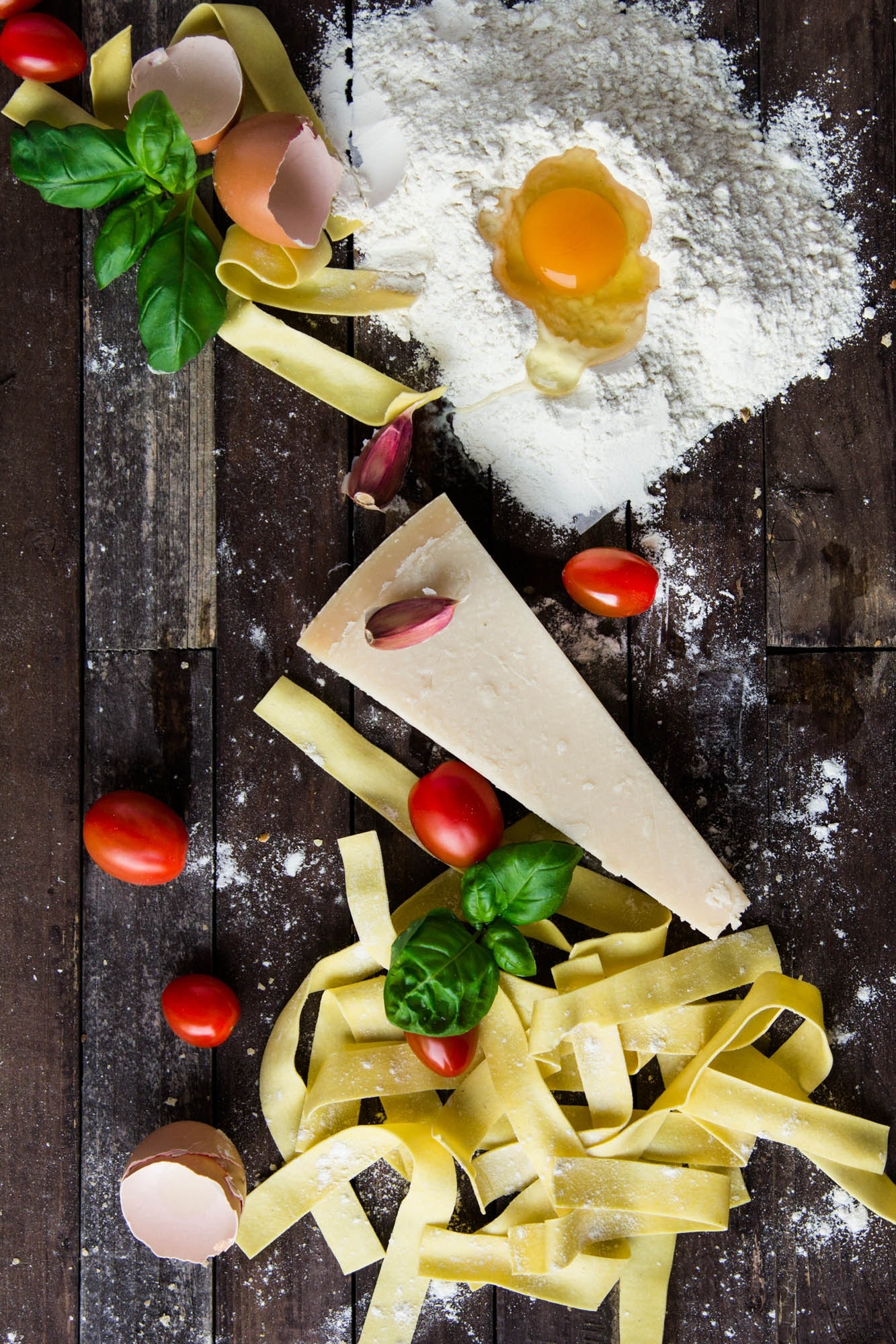 Pasta tomatoes and flour with egg shells on table photo