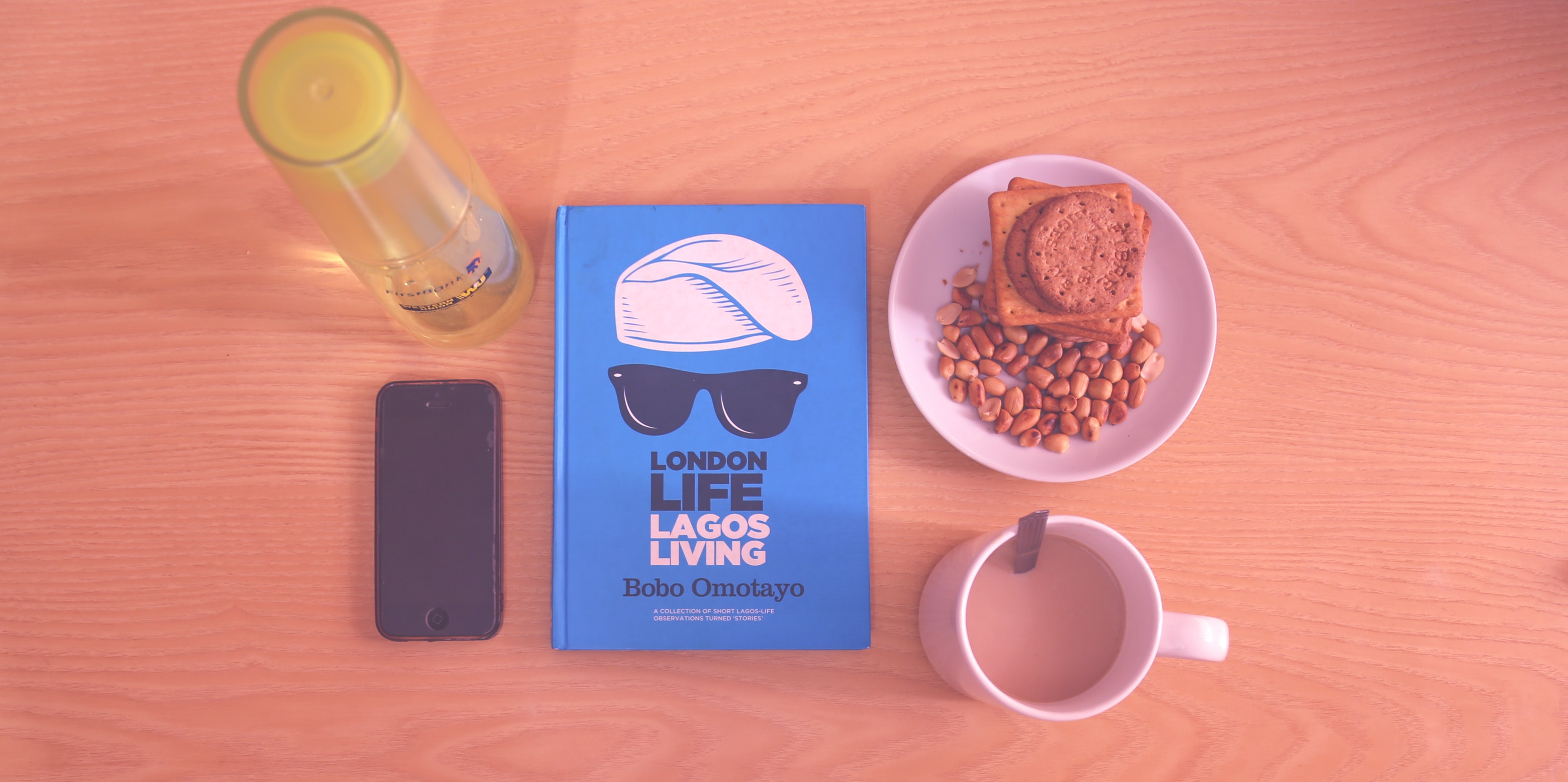 Peanuts and biscuits in white ceramic plate beside white ceramic mug near lagos living book photo