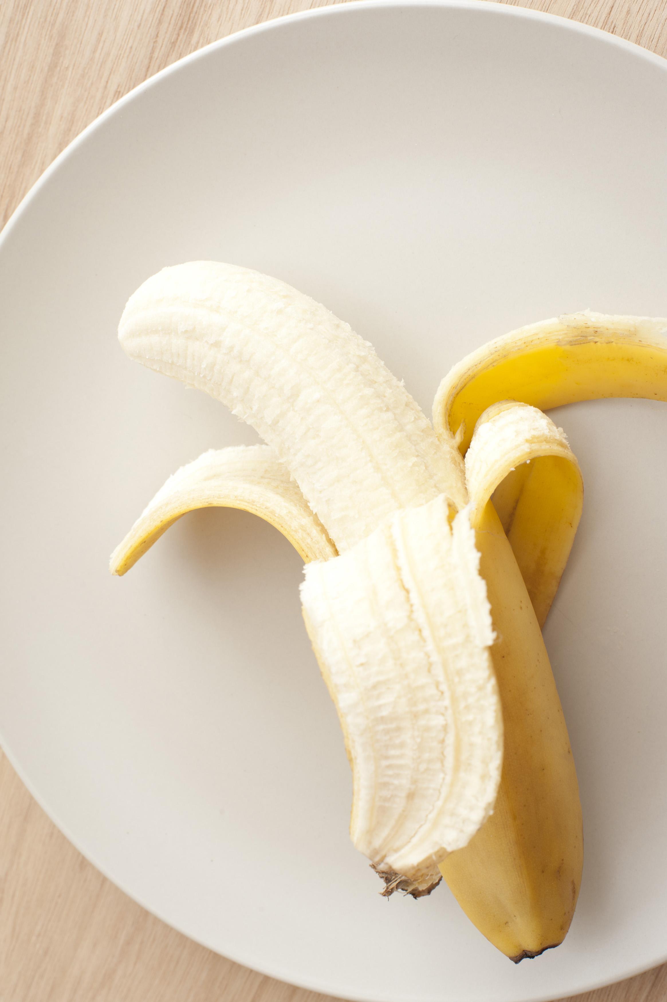 Peeled banana on a white plate - Free Stock Image
