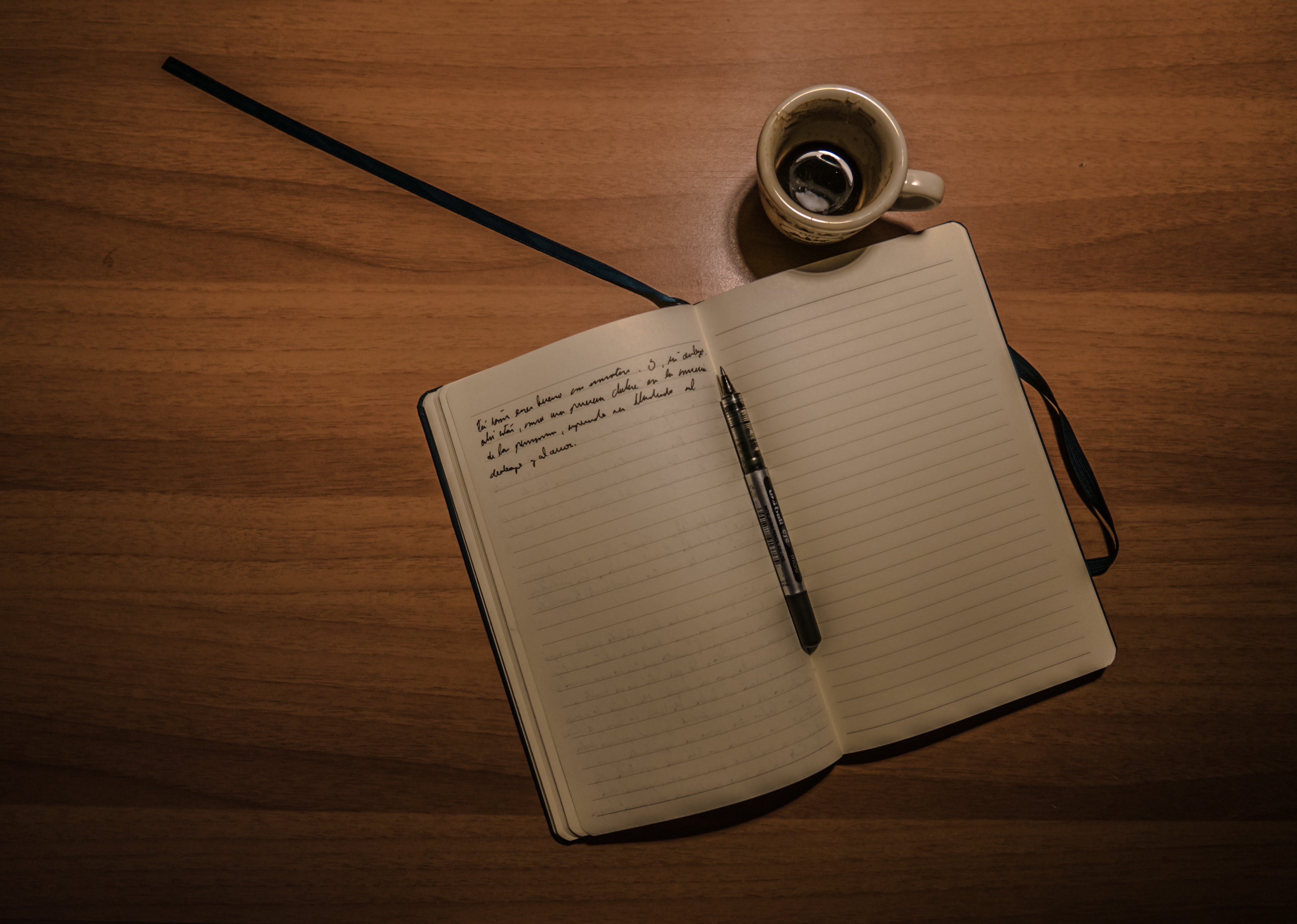Pen on notebook beside a teacup on brown wooden plank photo