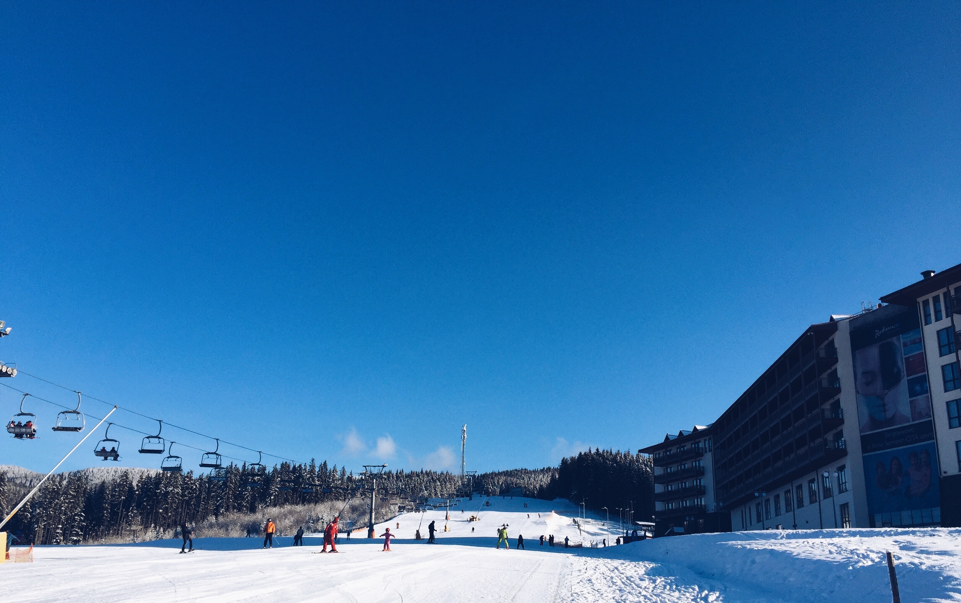 People on a snowy ski hill with a lift on the left and a hotel on the right photo