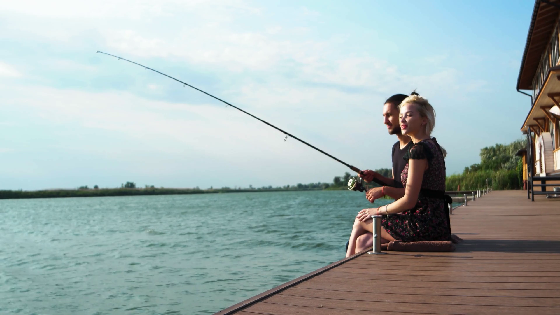happy lovers fishing on spinning together at sunbeam, sweet couple ...