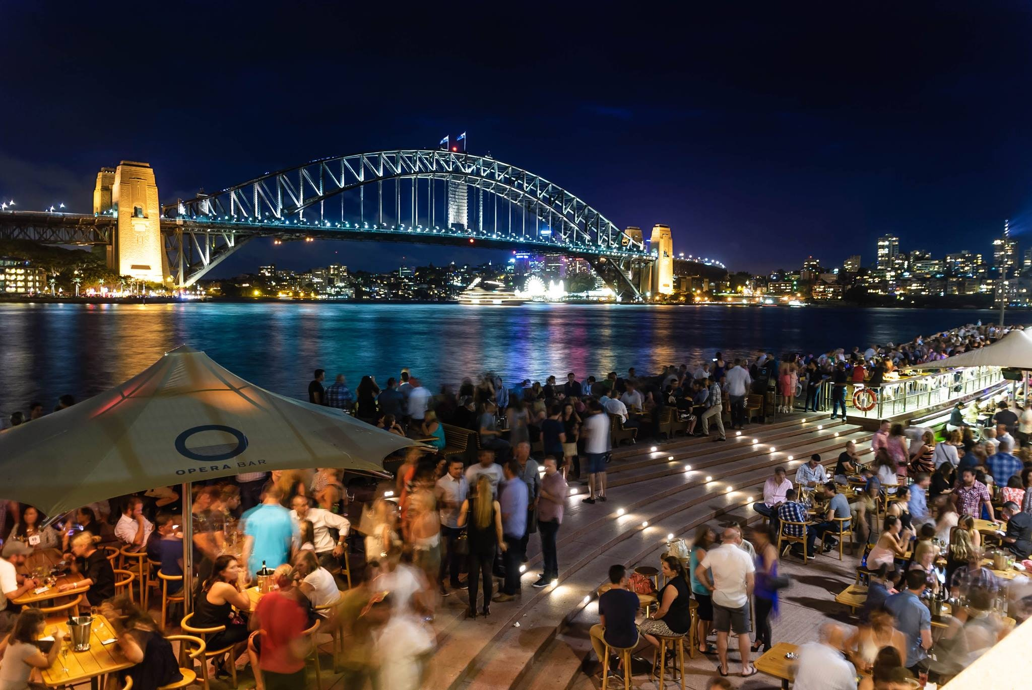 People sitting and standing near bridge during nighttime photo