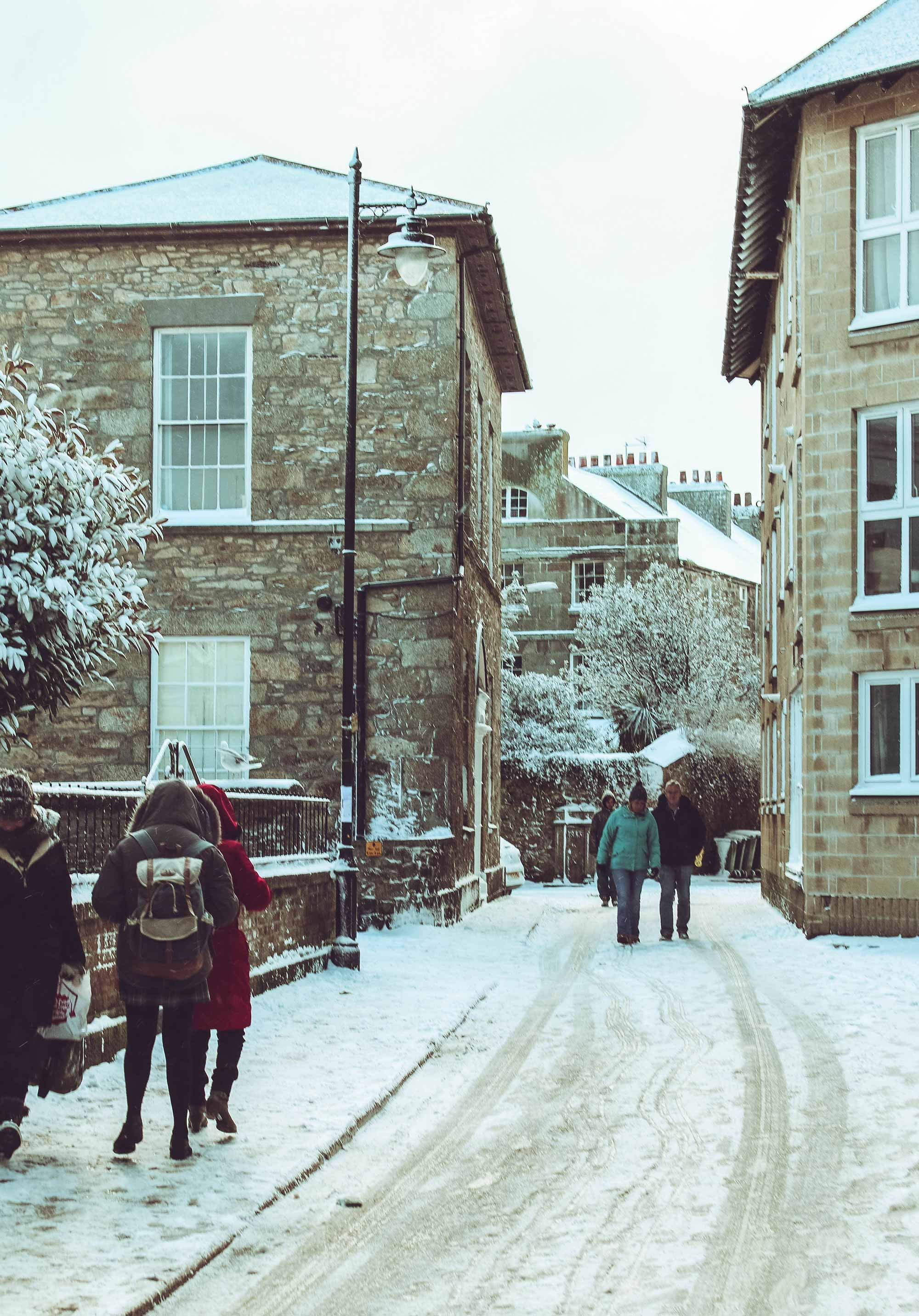 People walking on snow covered street photo