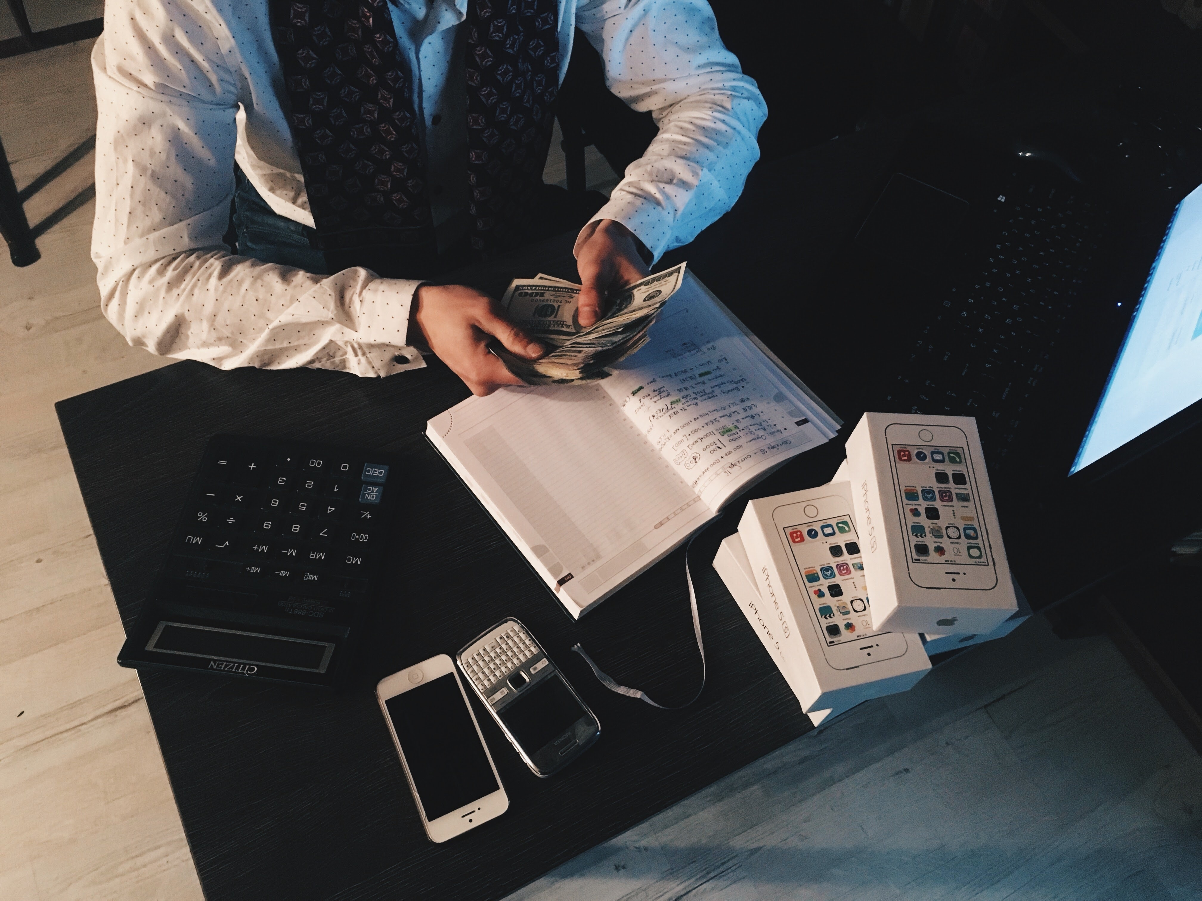 Person counting money with smartphones in front on desk photo