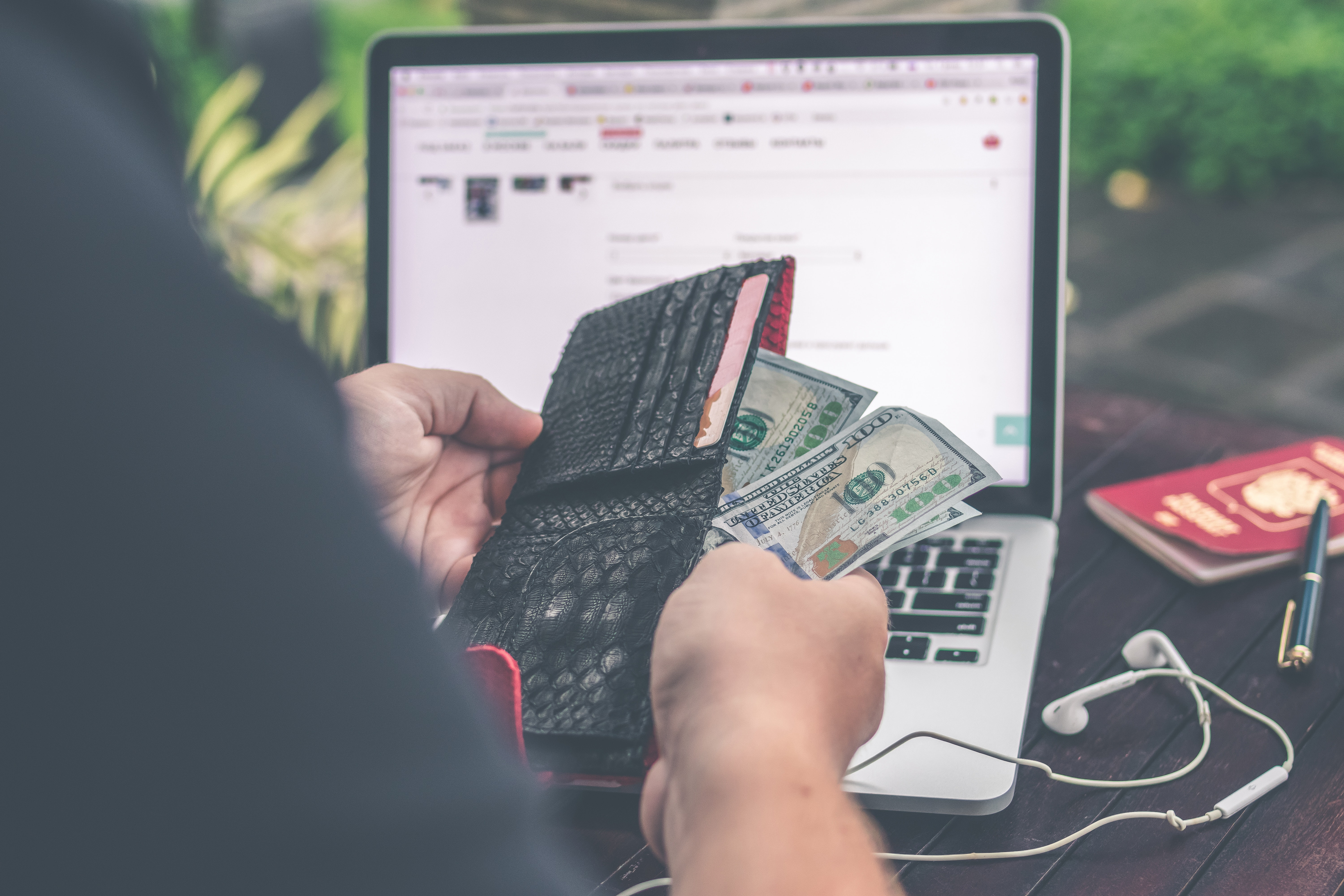 Person holding 10 us dollar banknote in front of gray and black laptop computer photo