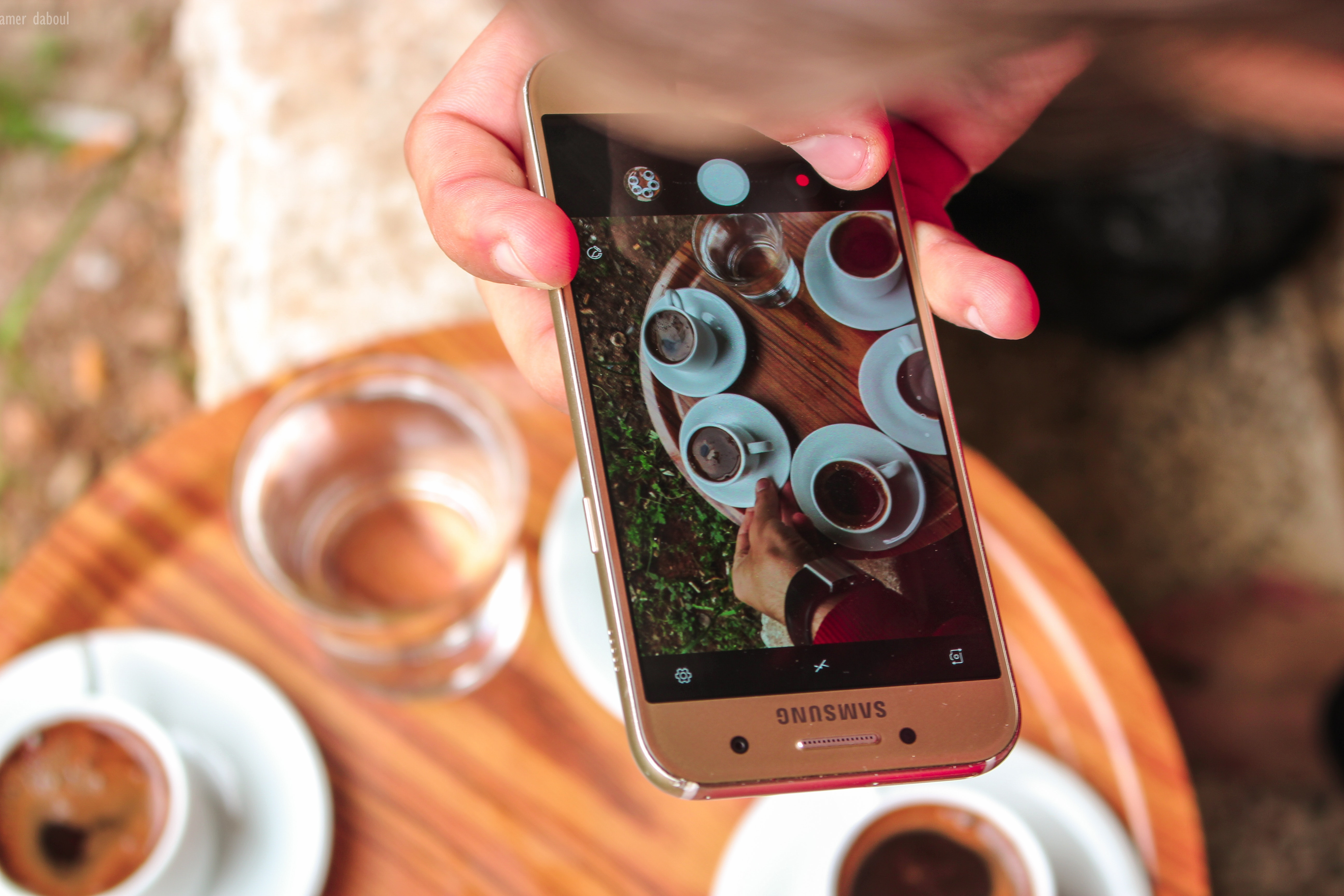 Person holding a samsung galaxy smartphone taking a picture on their coffees photo