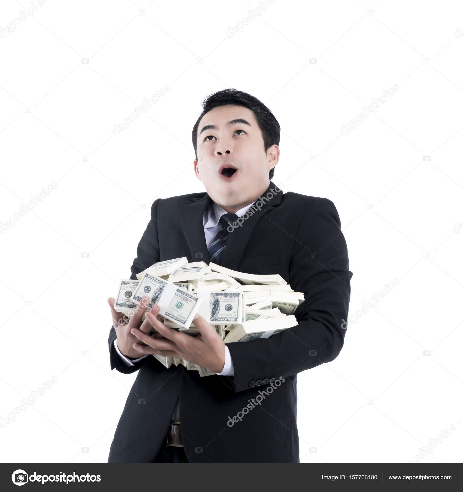 The cheerful young businessman holding a big pile of money in hi ...