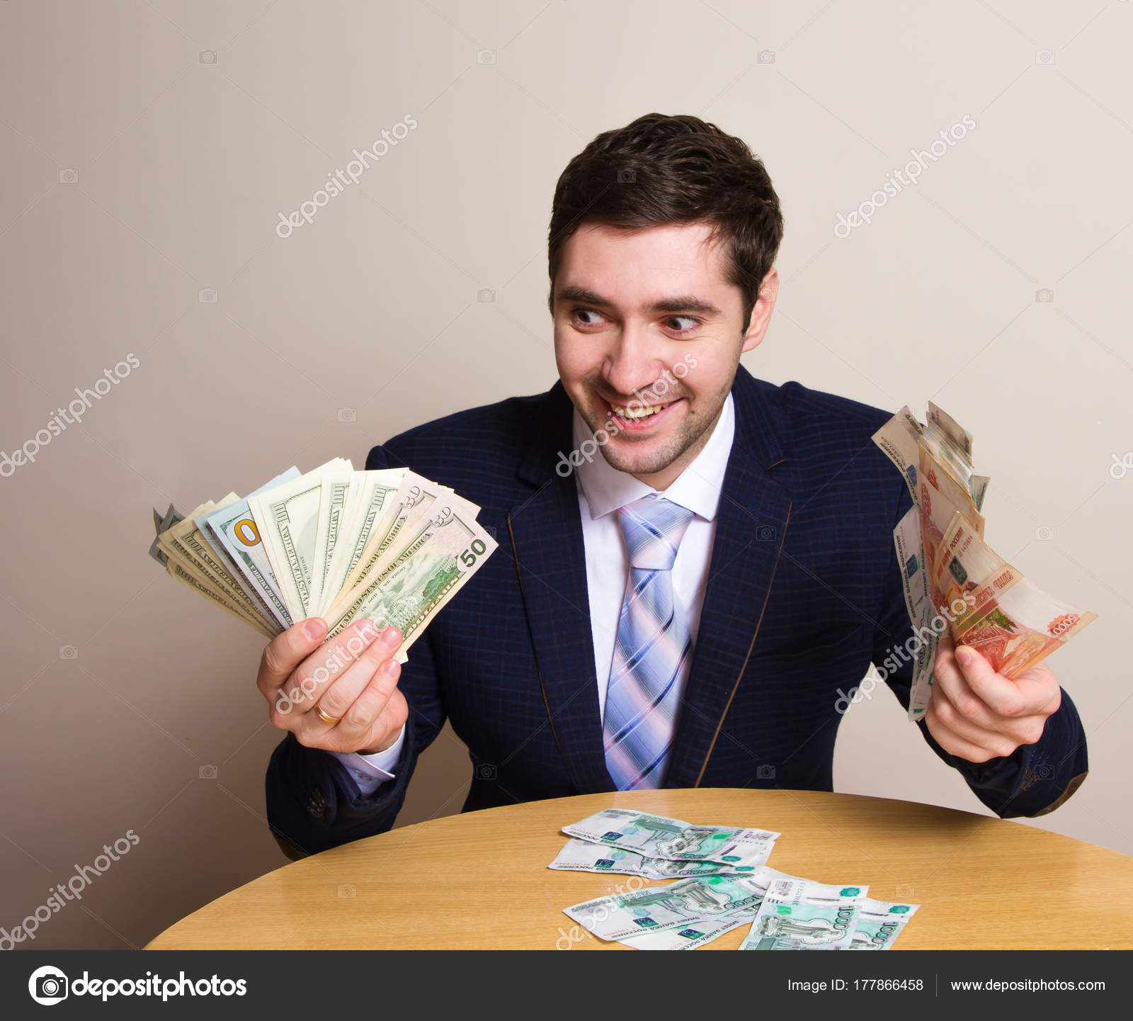 Businessman in suit holding money in his hands dollar and ruble ...