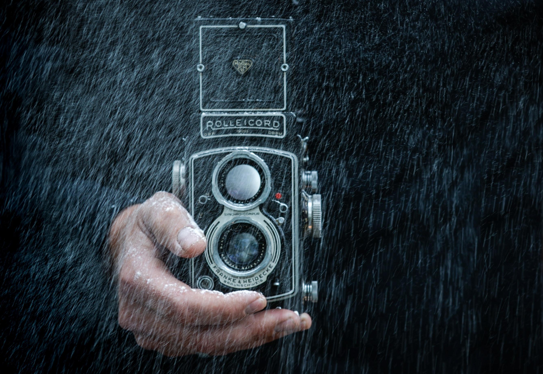 Person holding black camera photo