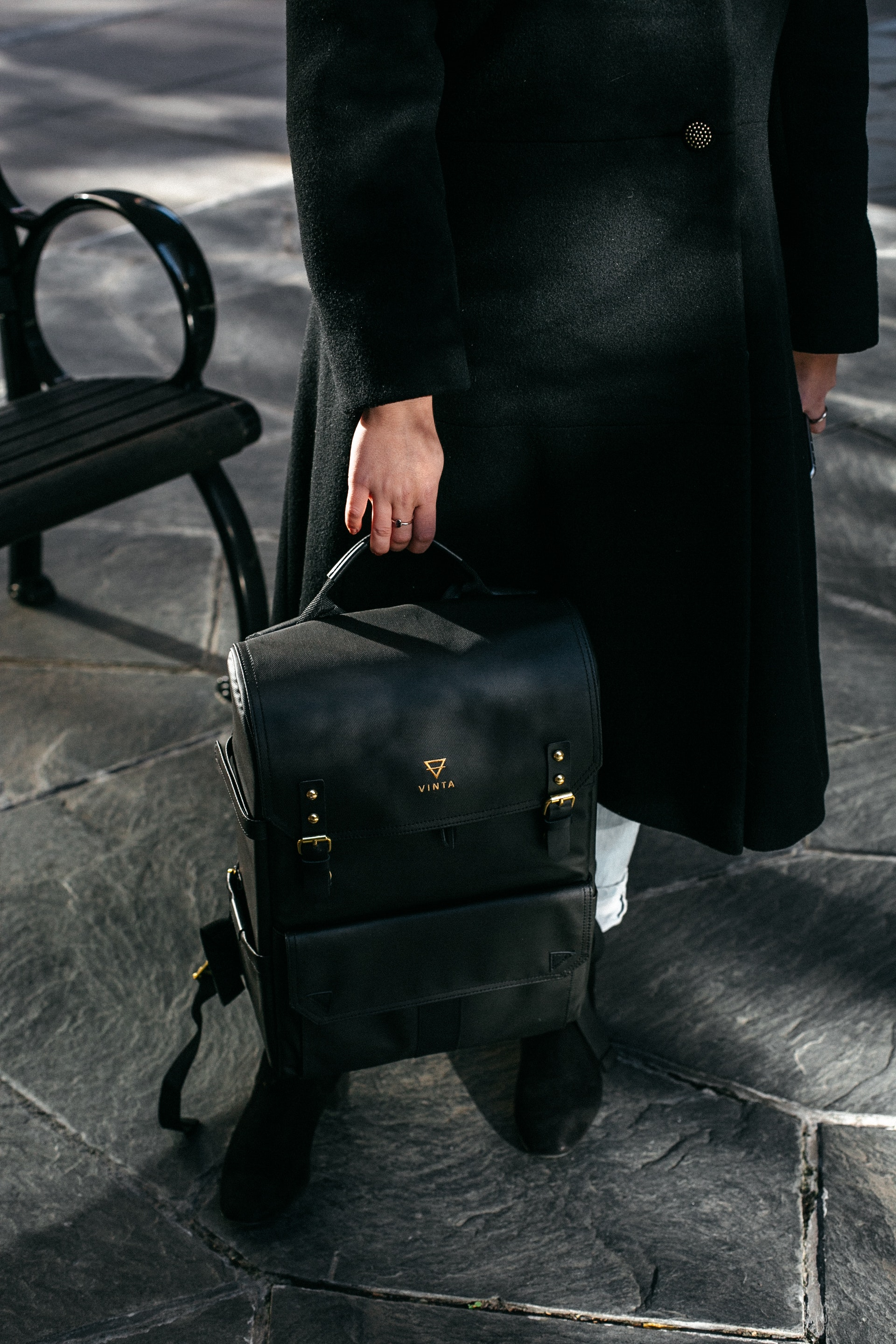 Person holding black leather backpack photo