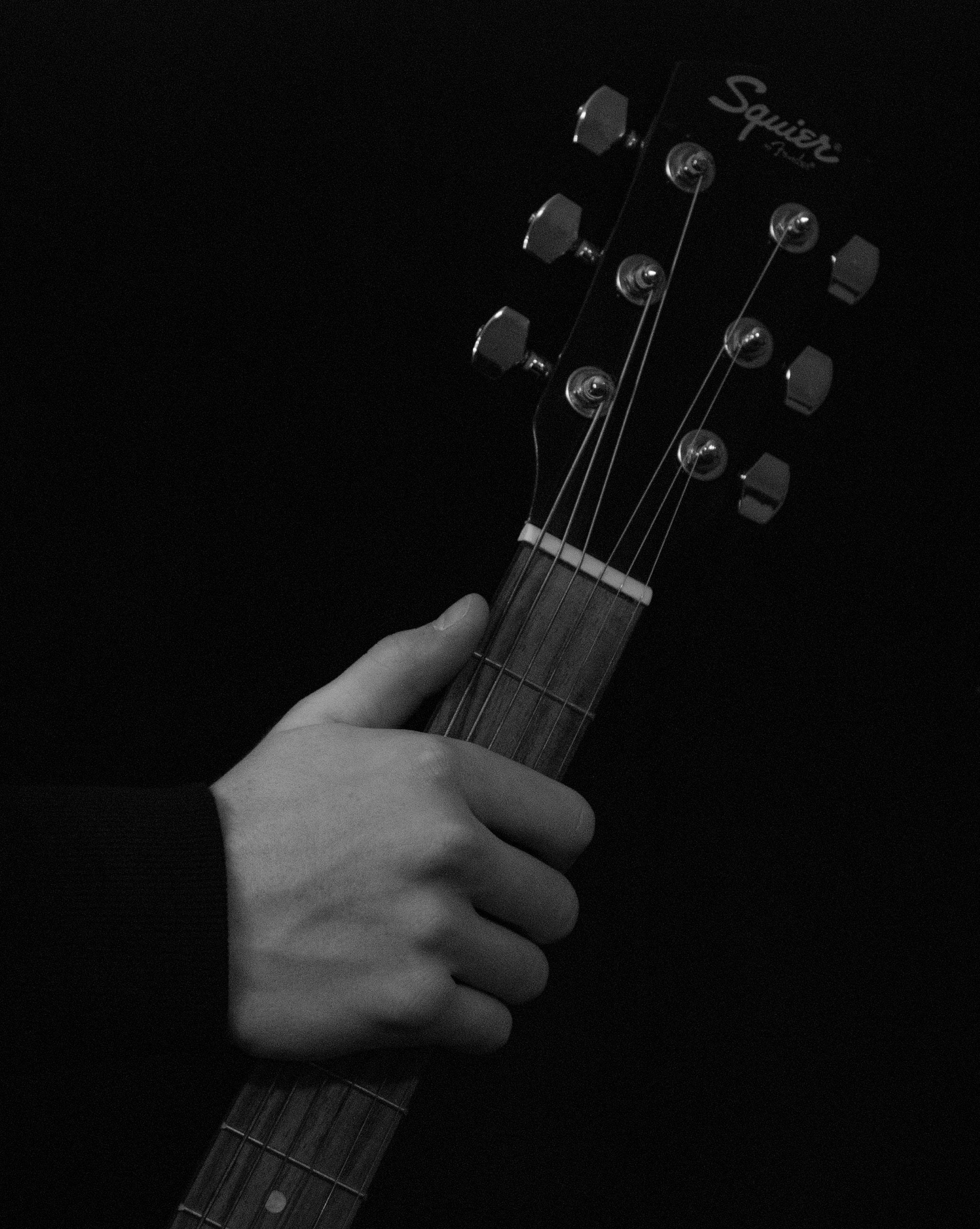 Person holding black squier fender guitar photo