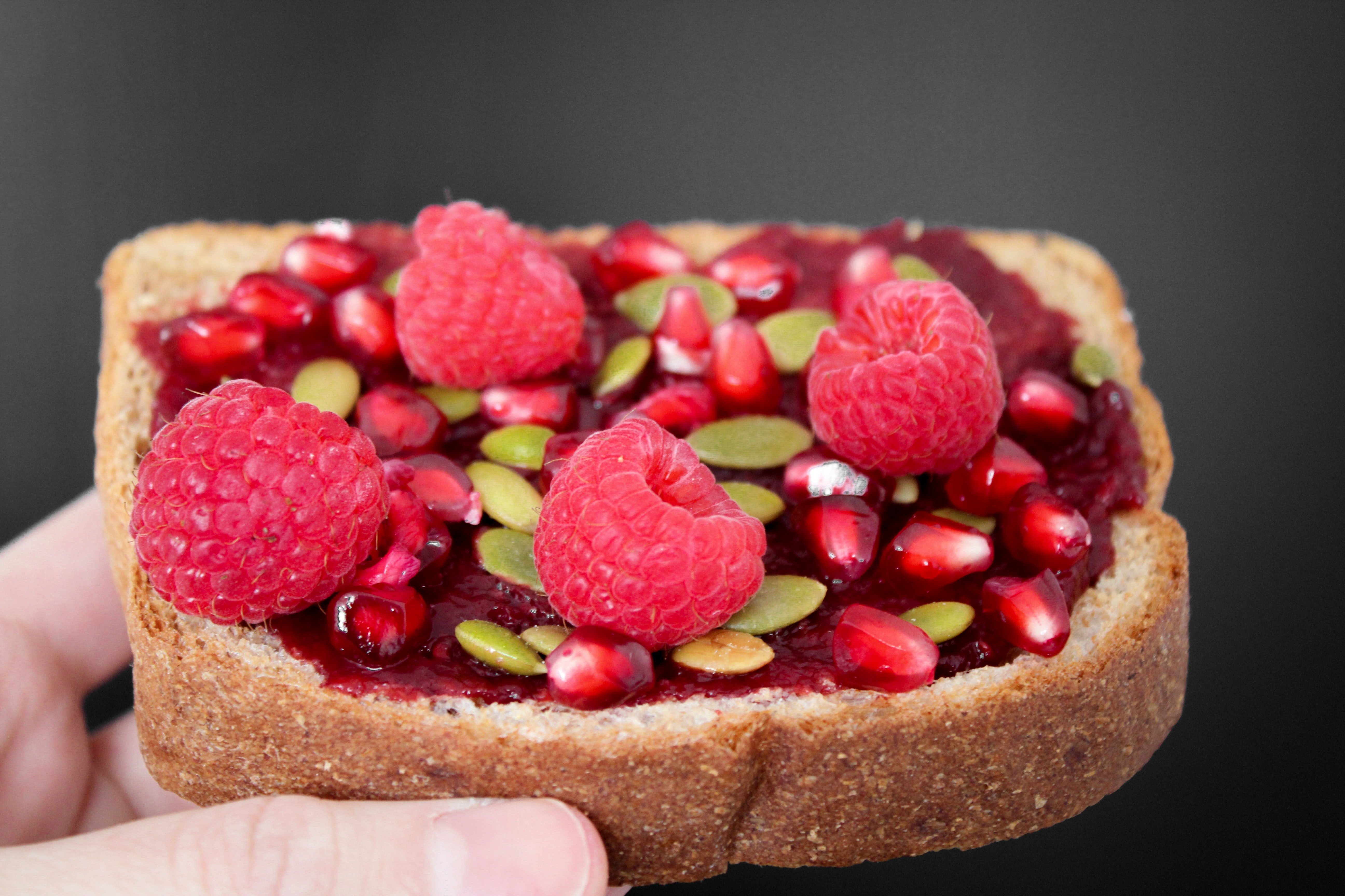 Person holding brown bread with strawberries photo