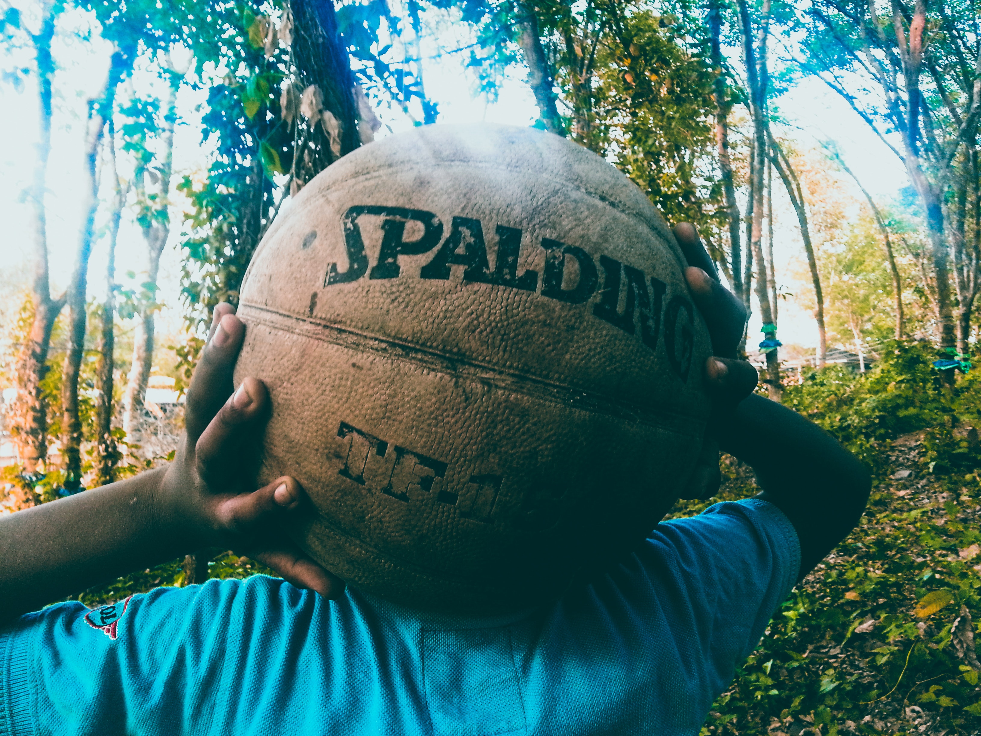 Person holding brown spalding basketball photo