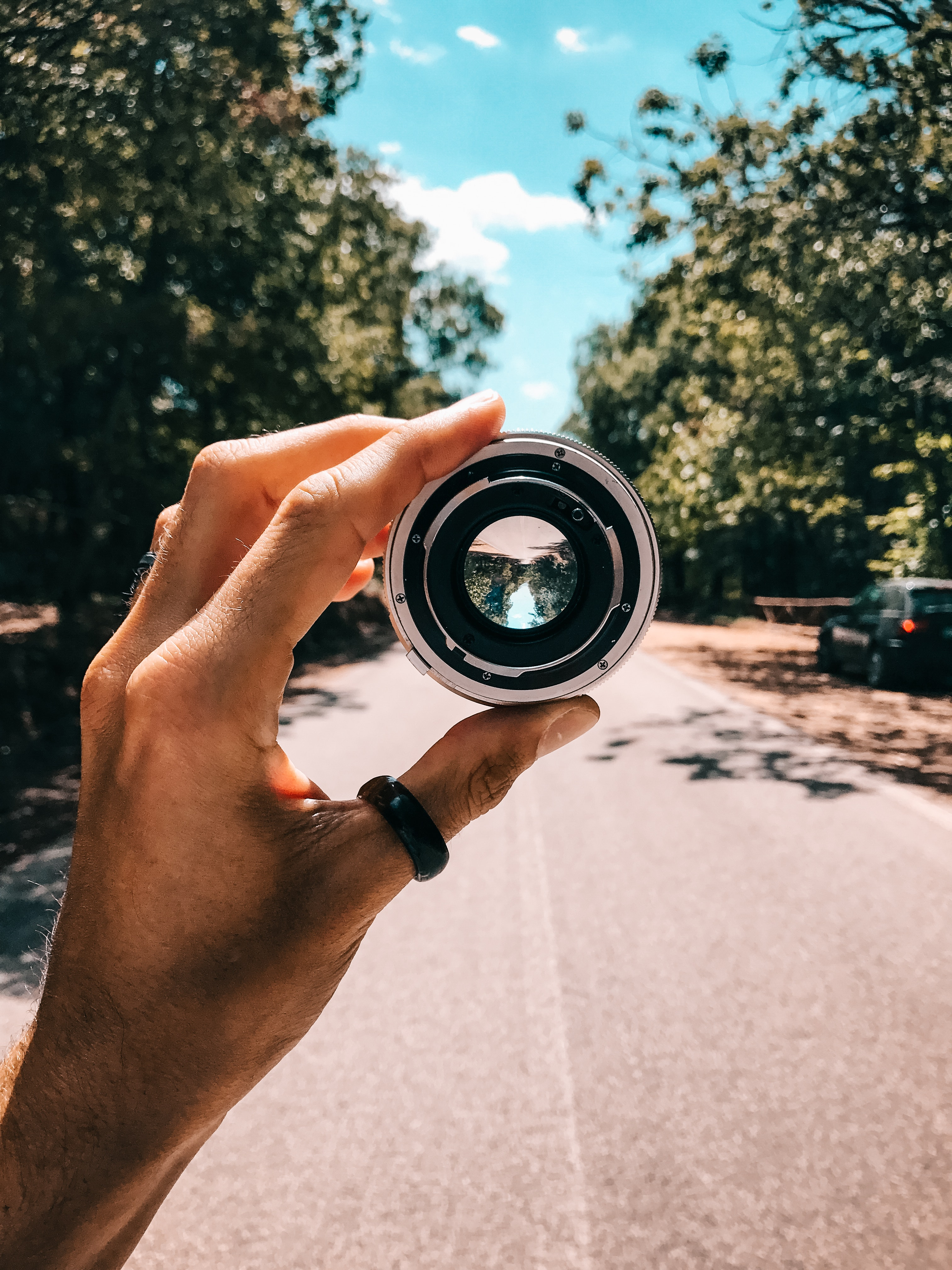 Person holding camera lens in the middle of street under blue sky photo