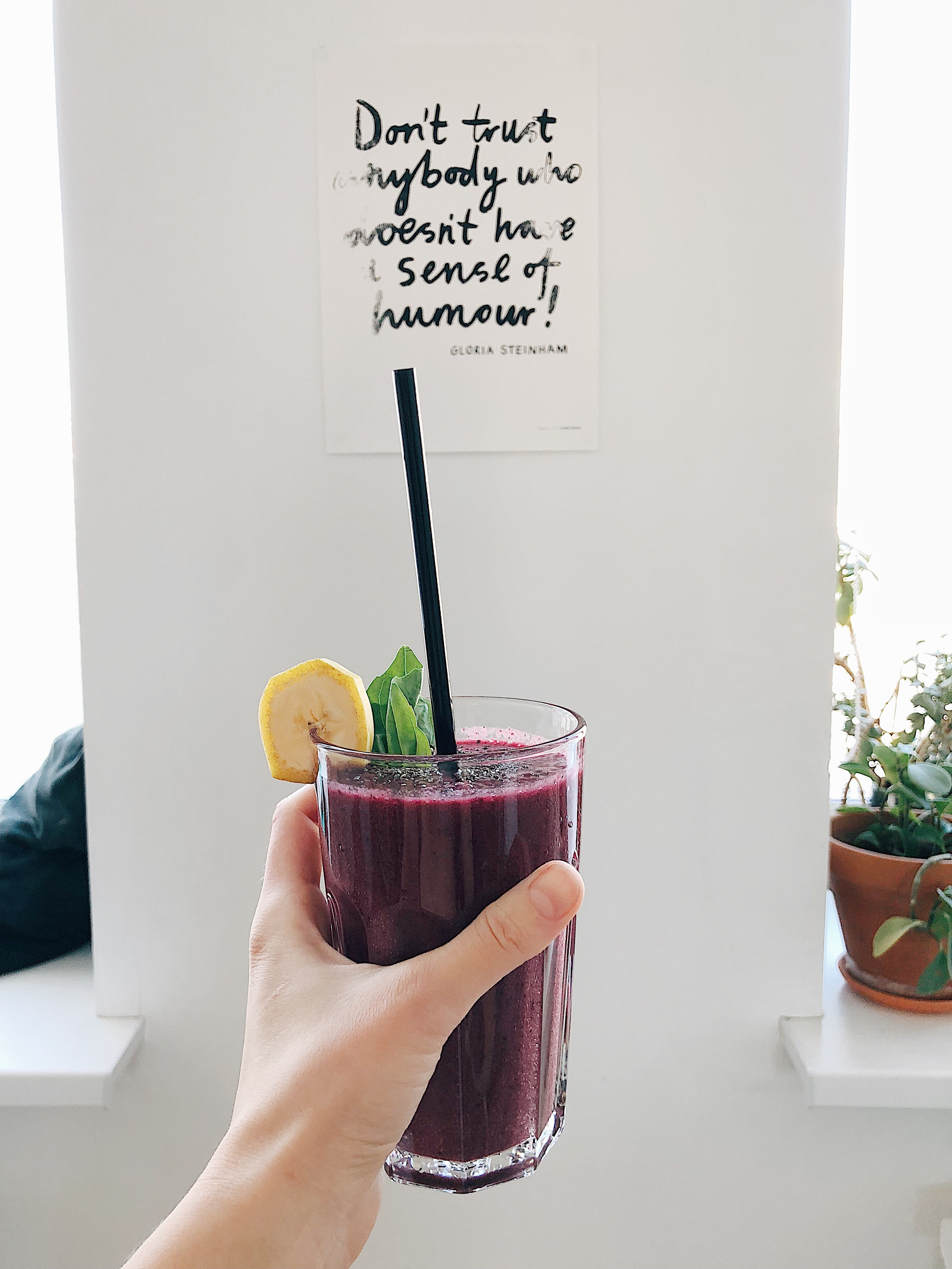Person holding clear drinking glass with purple smoothie with quotation decor photo