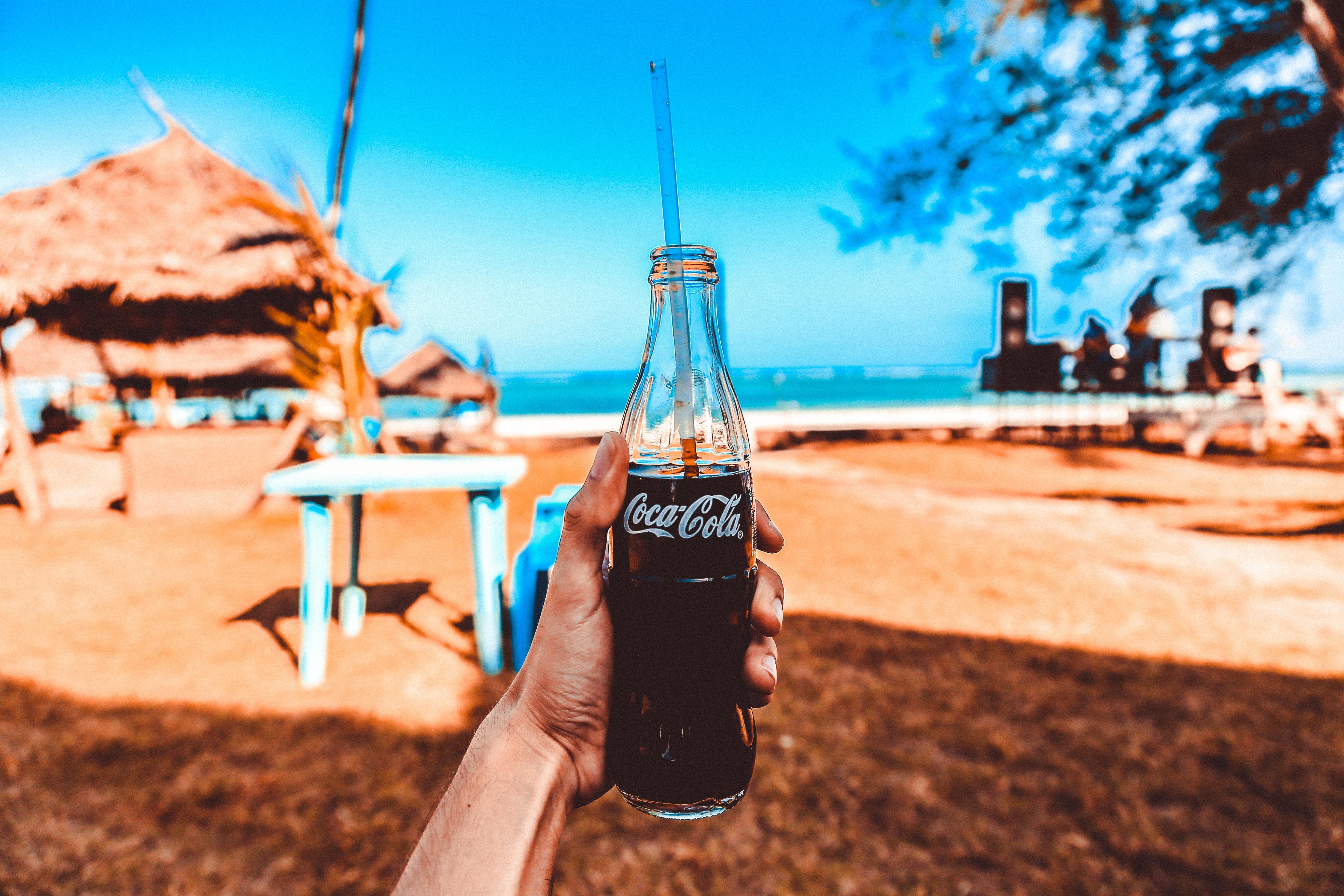 Person holding coca-cola glass bottle photo