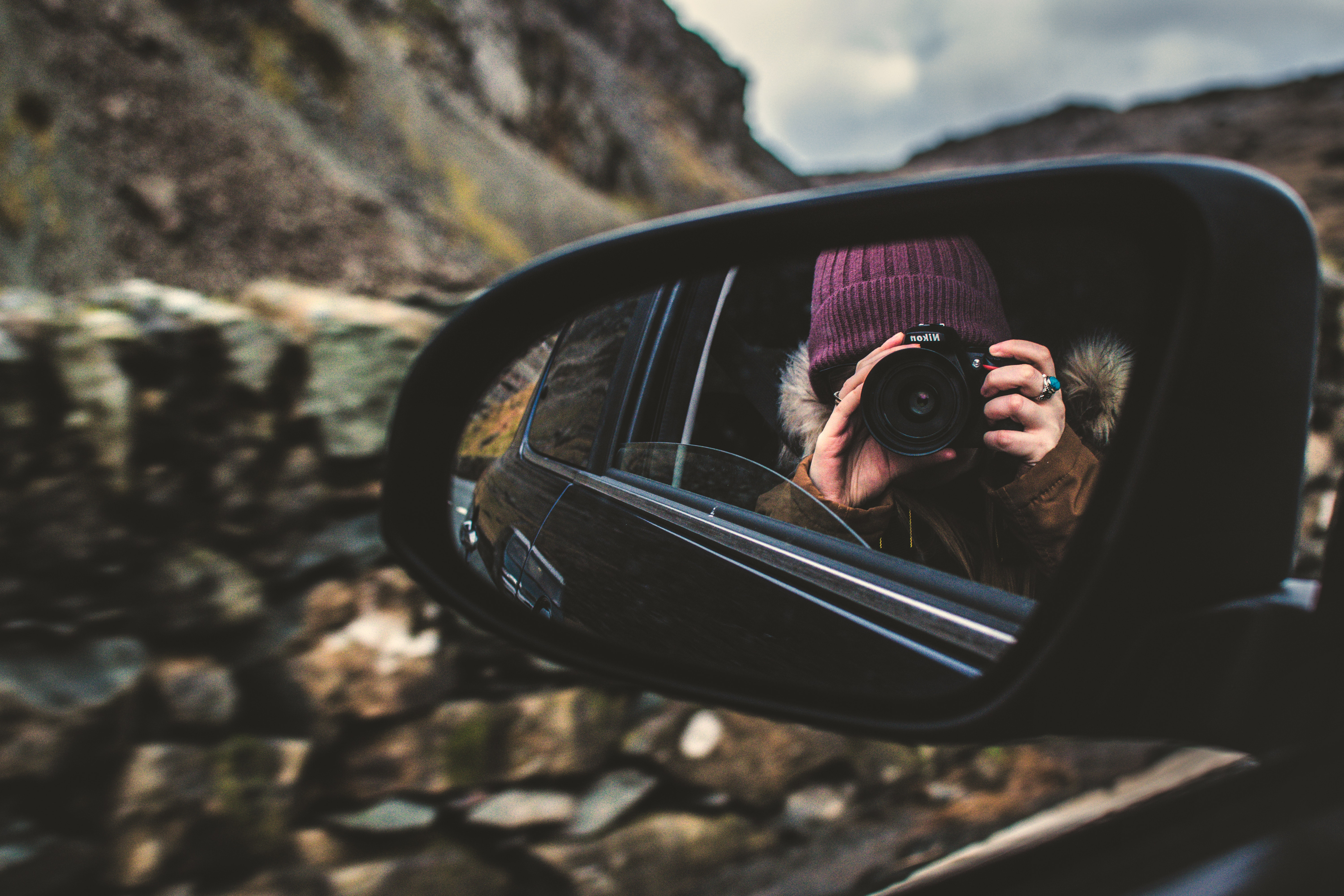 Person holding dslr camera reflected on black framed wing mirror photo