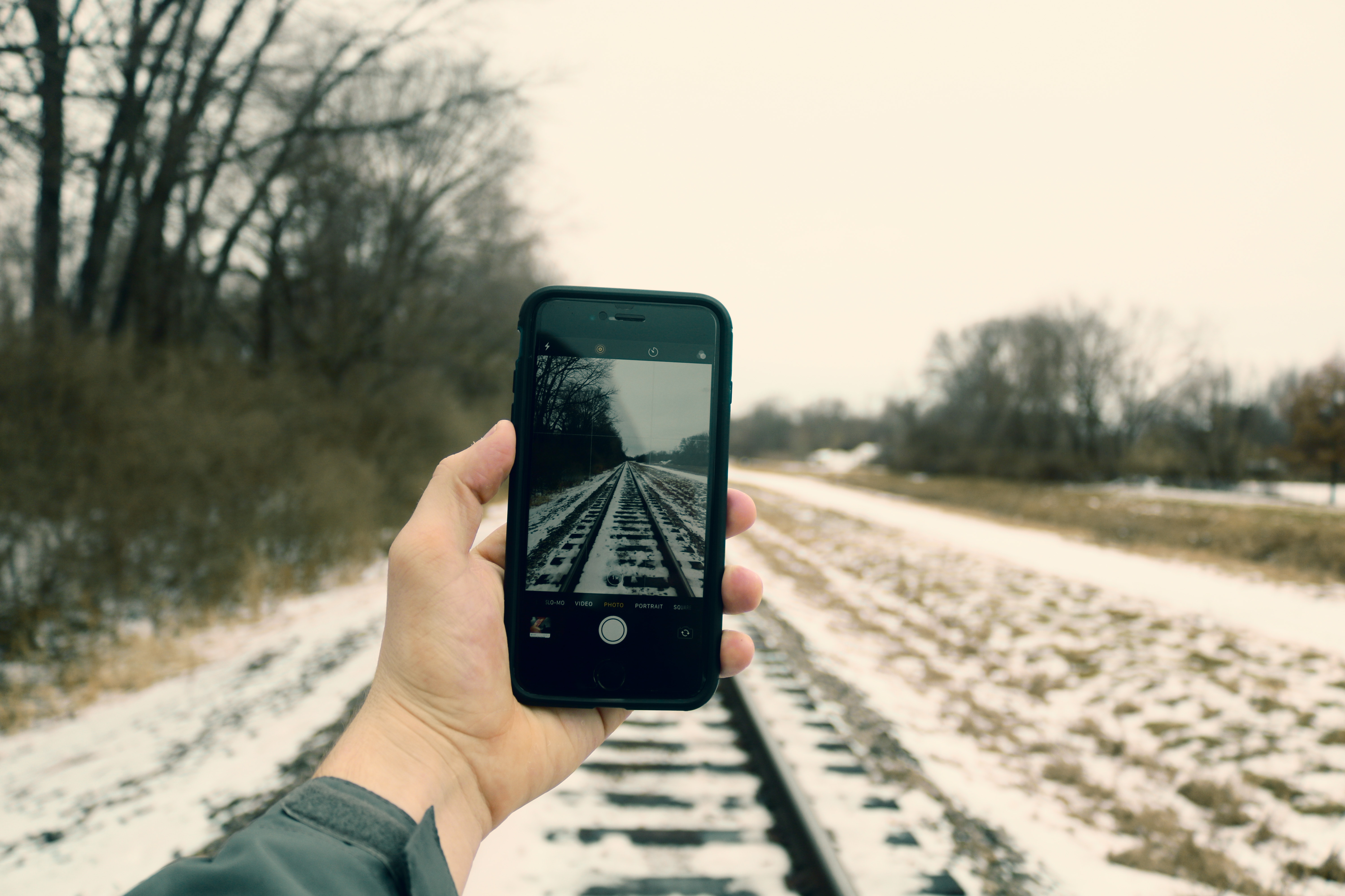Person Holding Iphone Taking Photo of Train Rails, Blur, Phone, Winter, Trees, HQ Photo