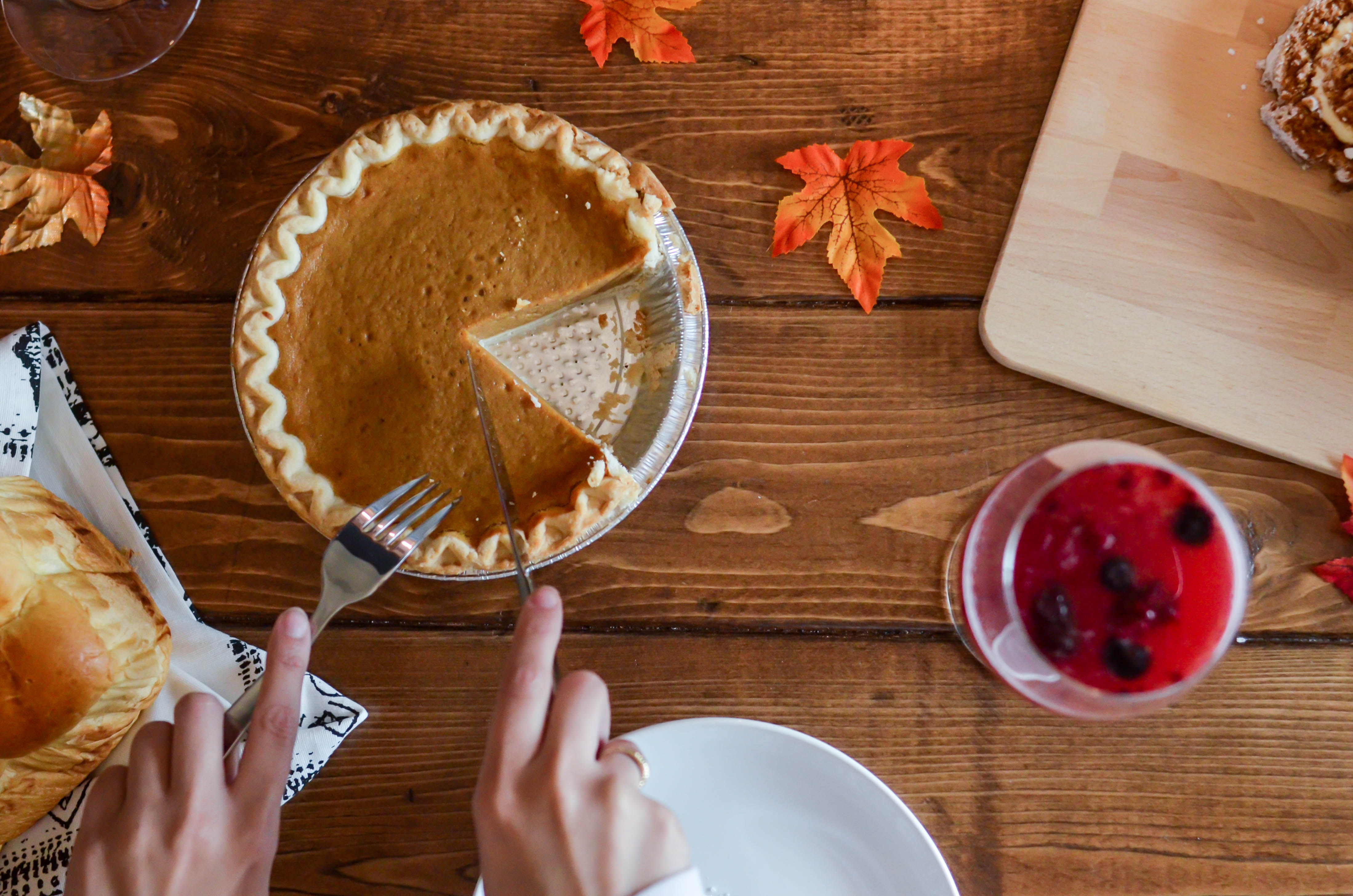 Person holding knife and fork cutting slice of pie on brown wooden table photo