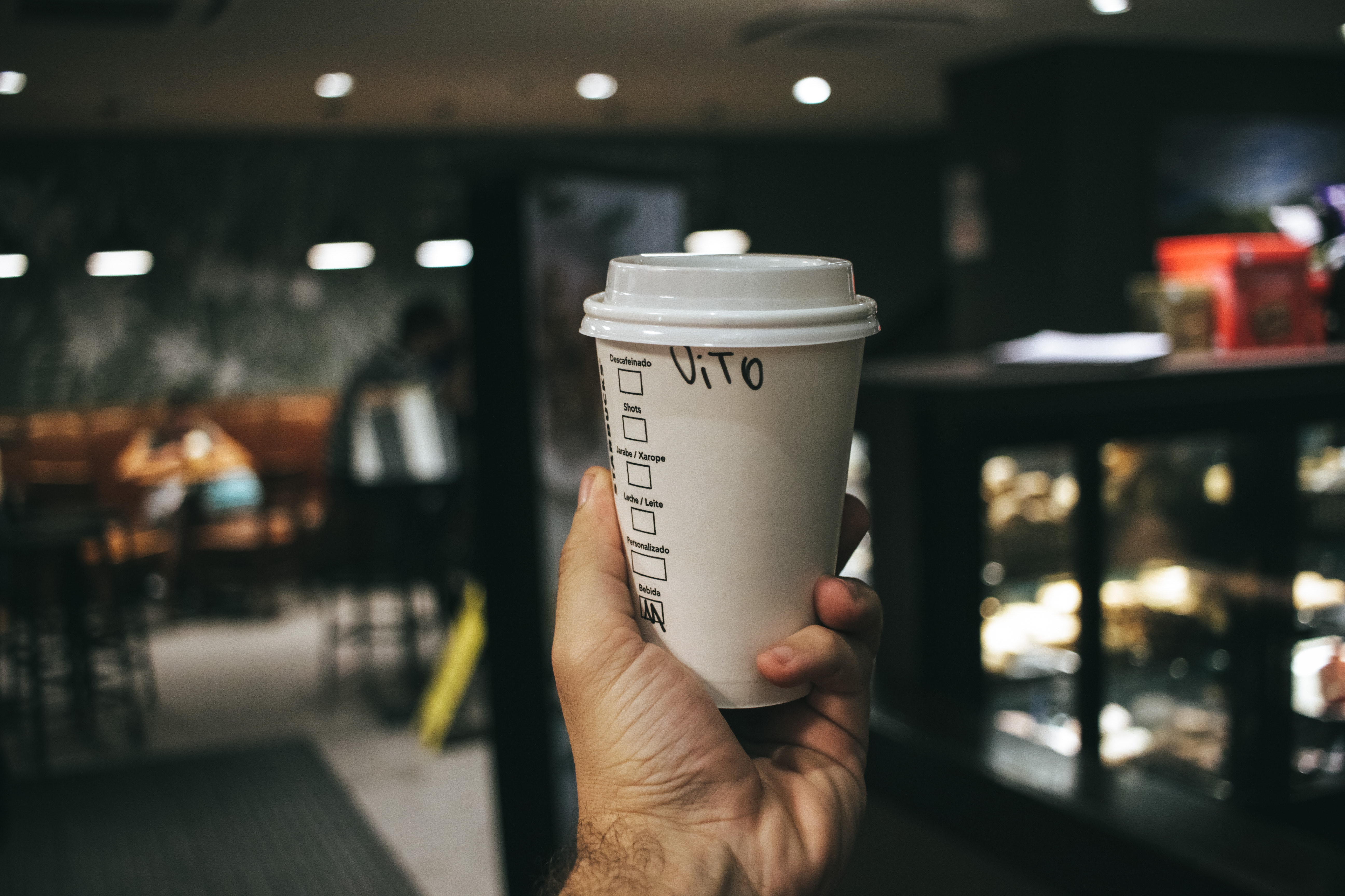 Person holding labeled disposable cup photo
