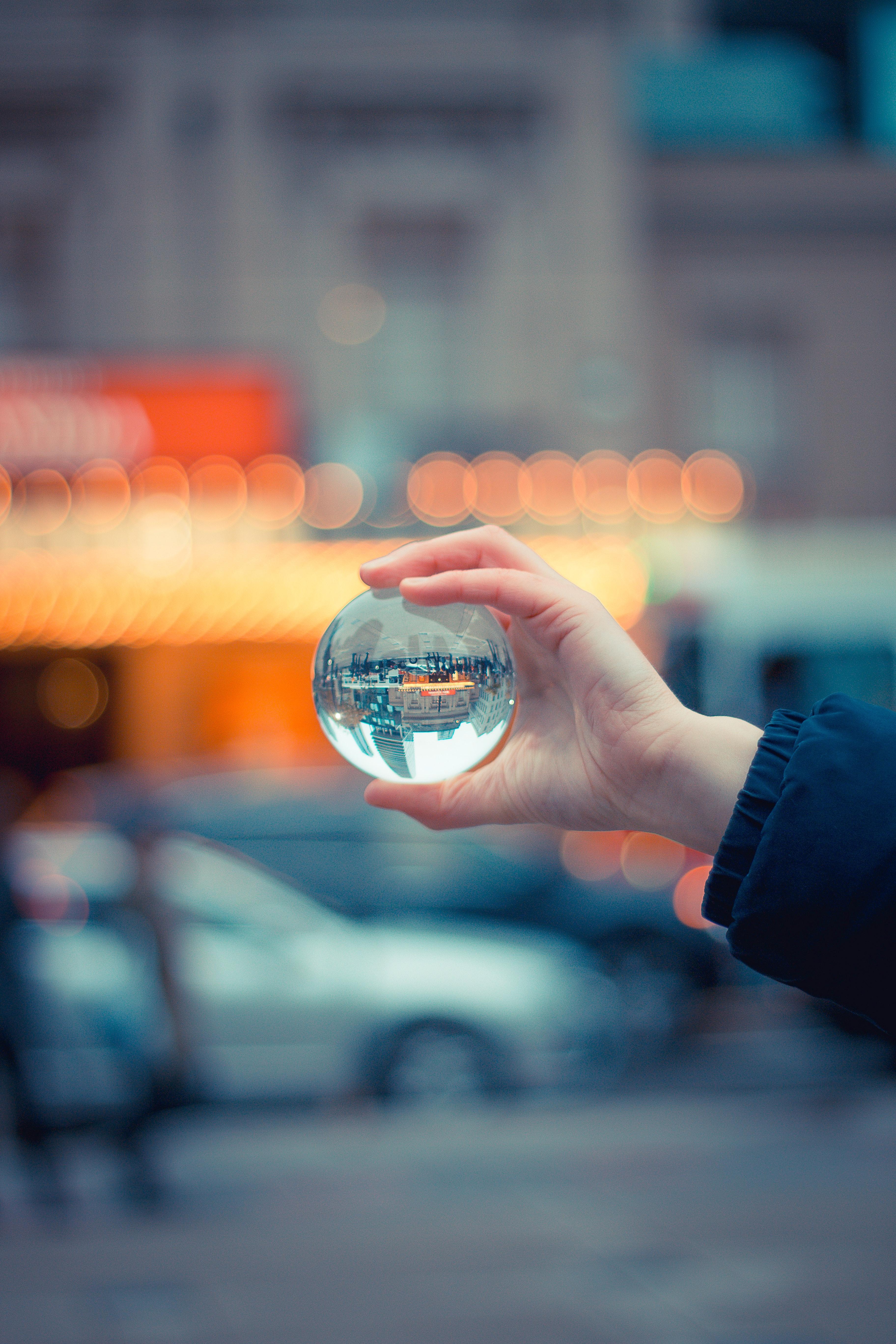 Person holding round glass ball macro shot photo