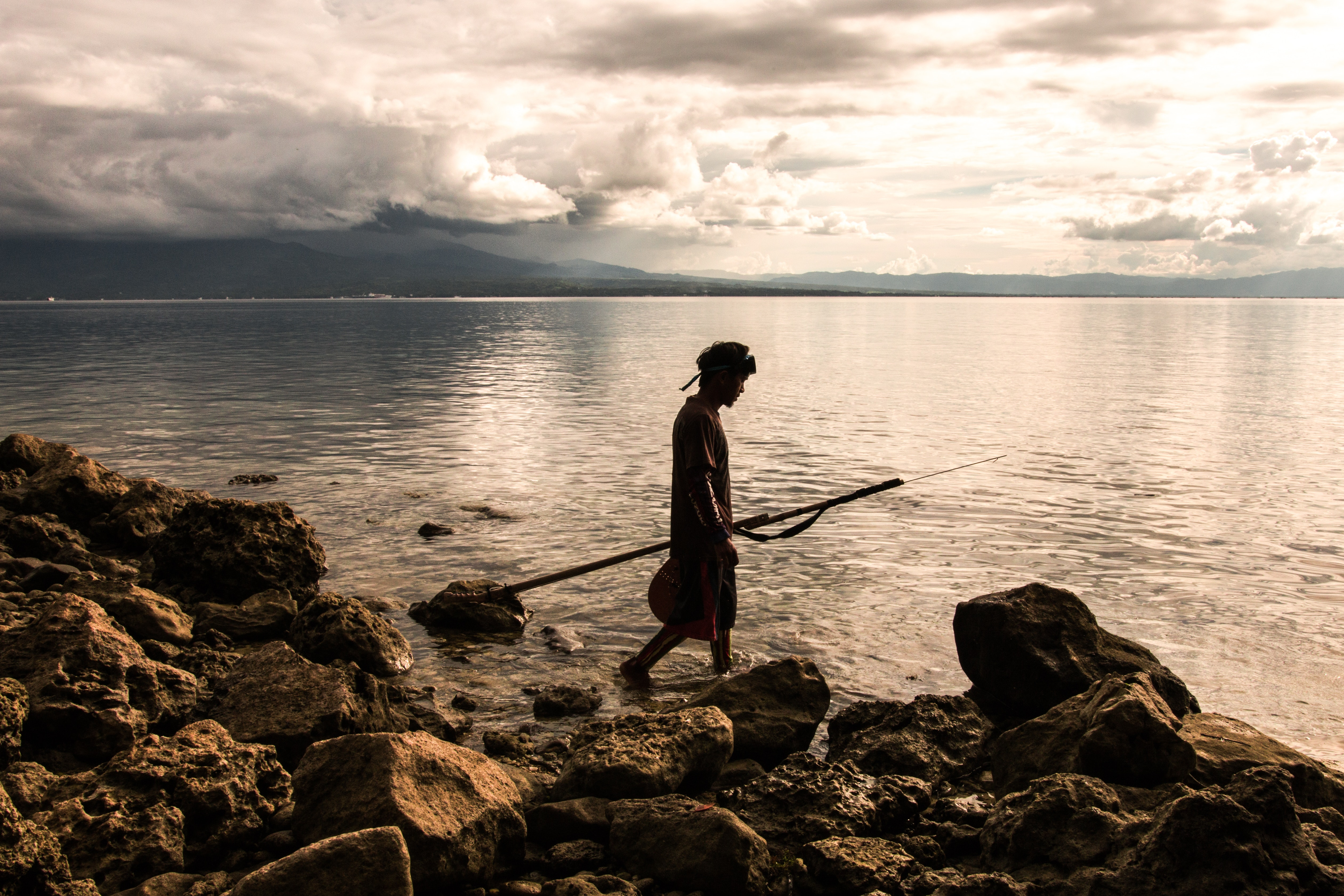 Person holding spear beside body of water photo