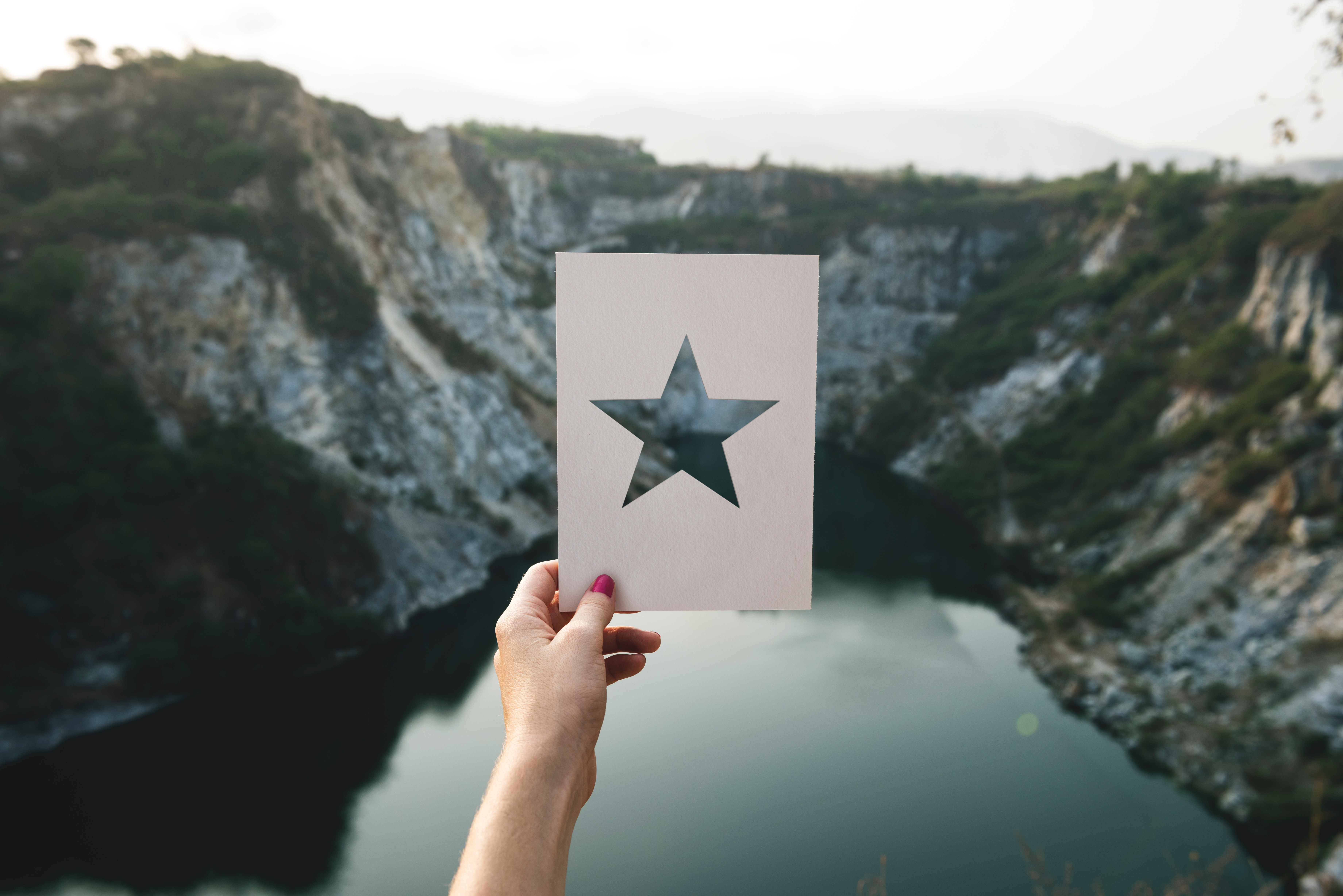 Person holding star cutout paper facing mountain photo