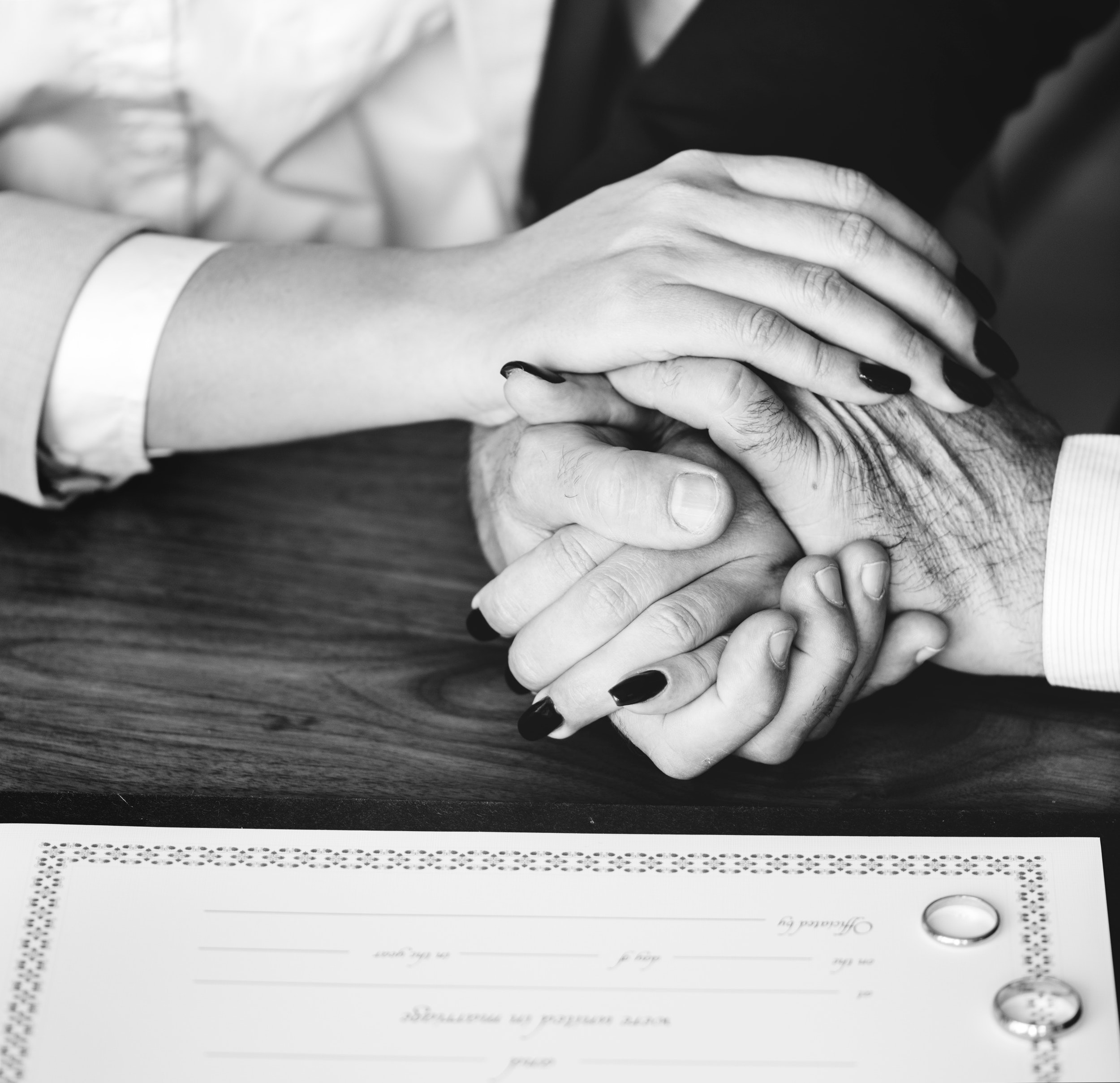 Person holding their hands on brown wooden table photo