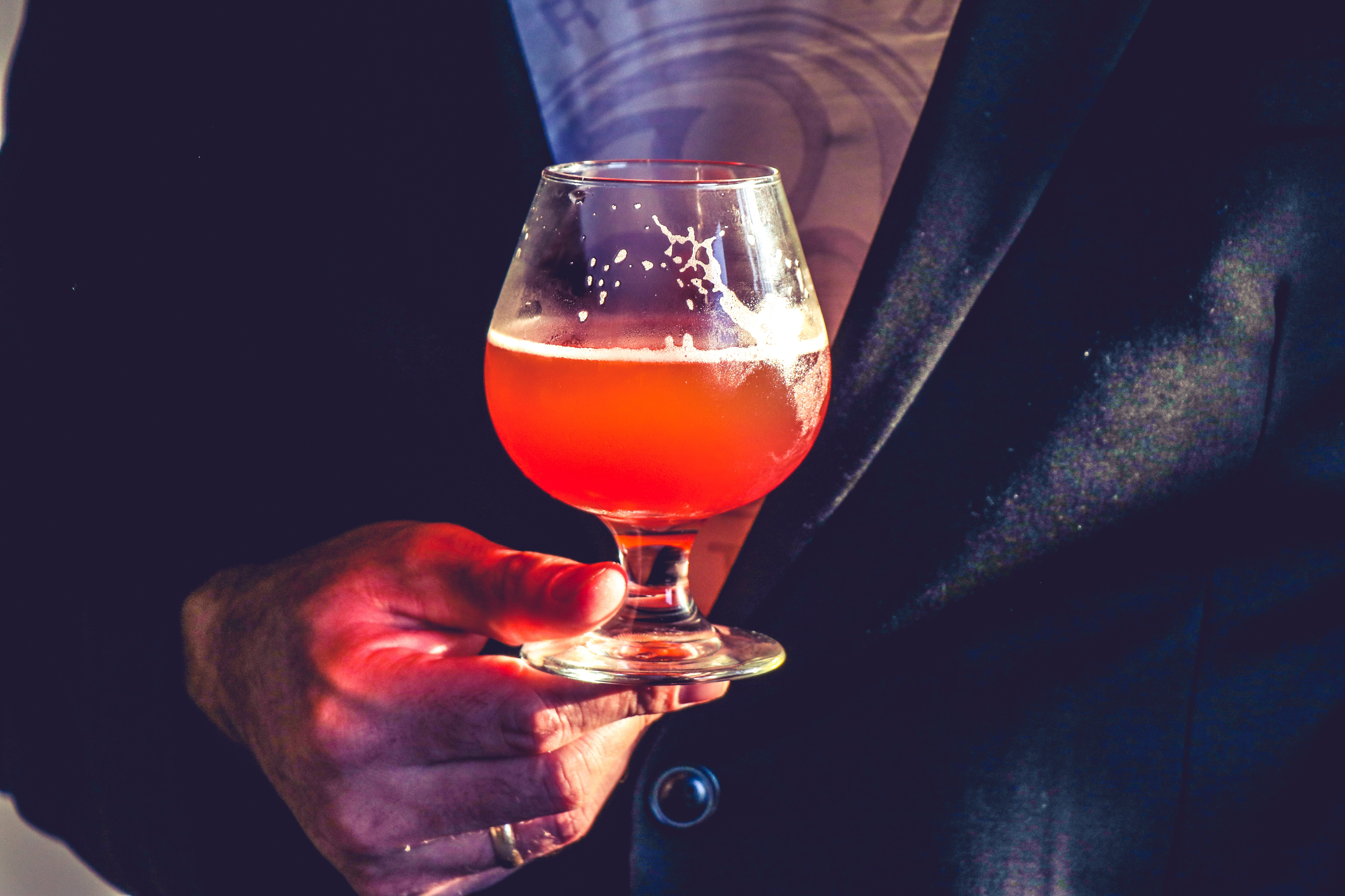 Person holds clear glass snifter with red beverage photo