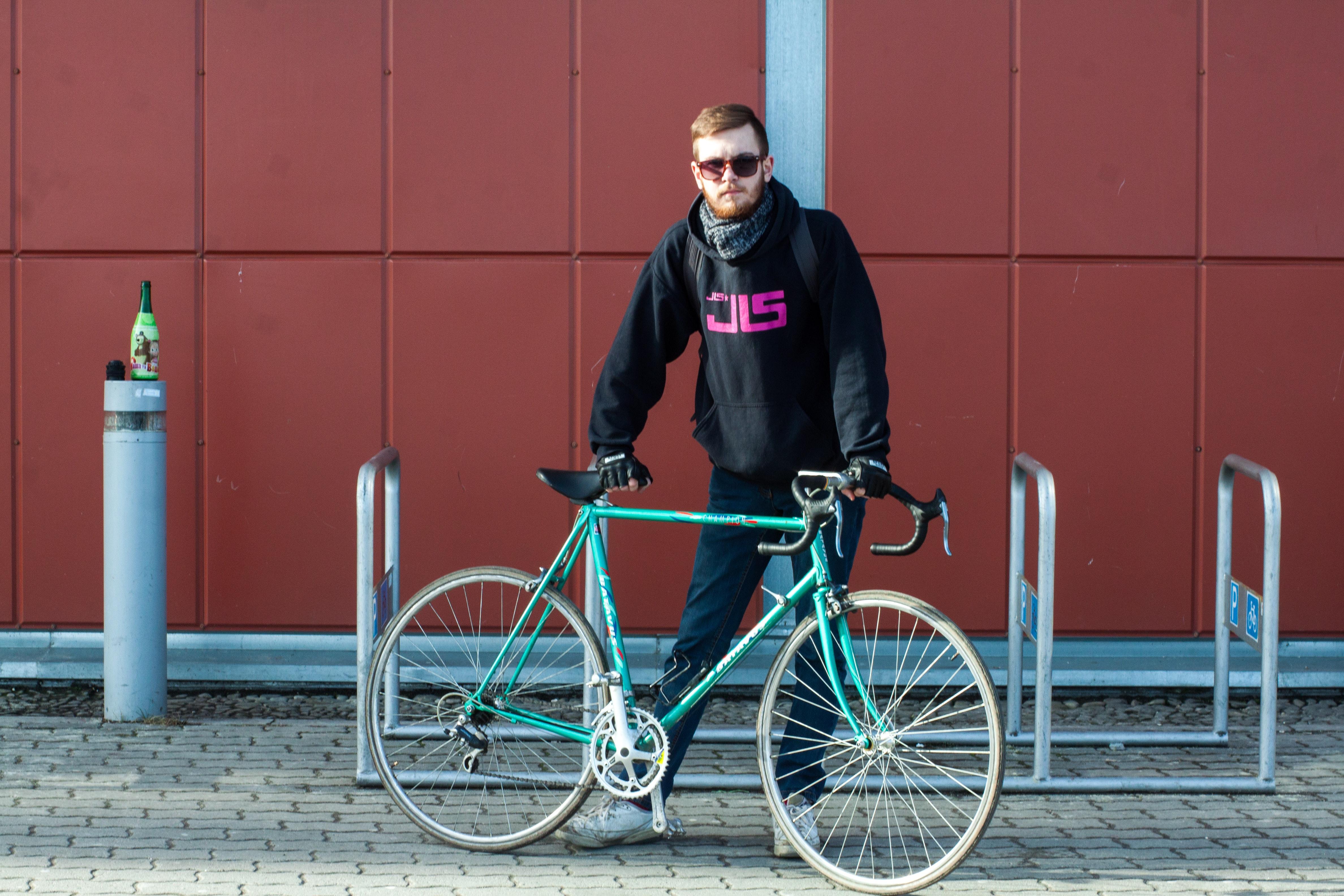 Person in black hoodie holding green bike photo