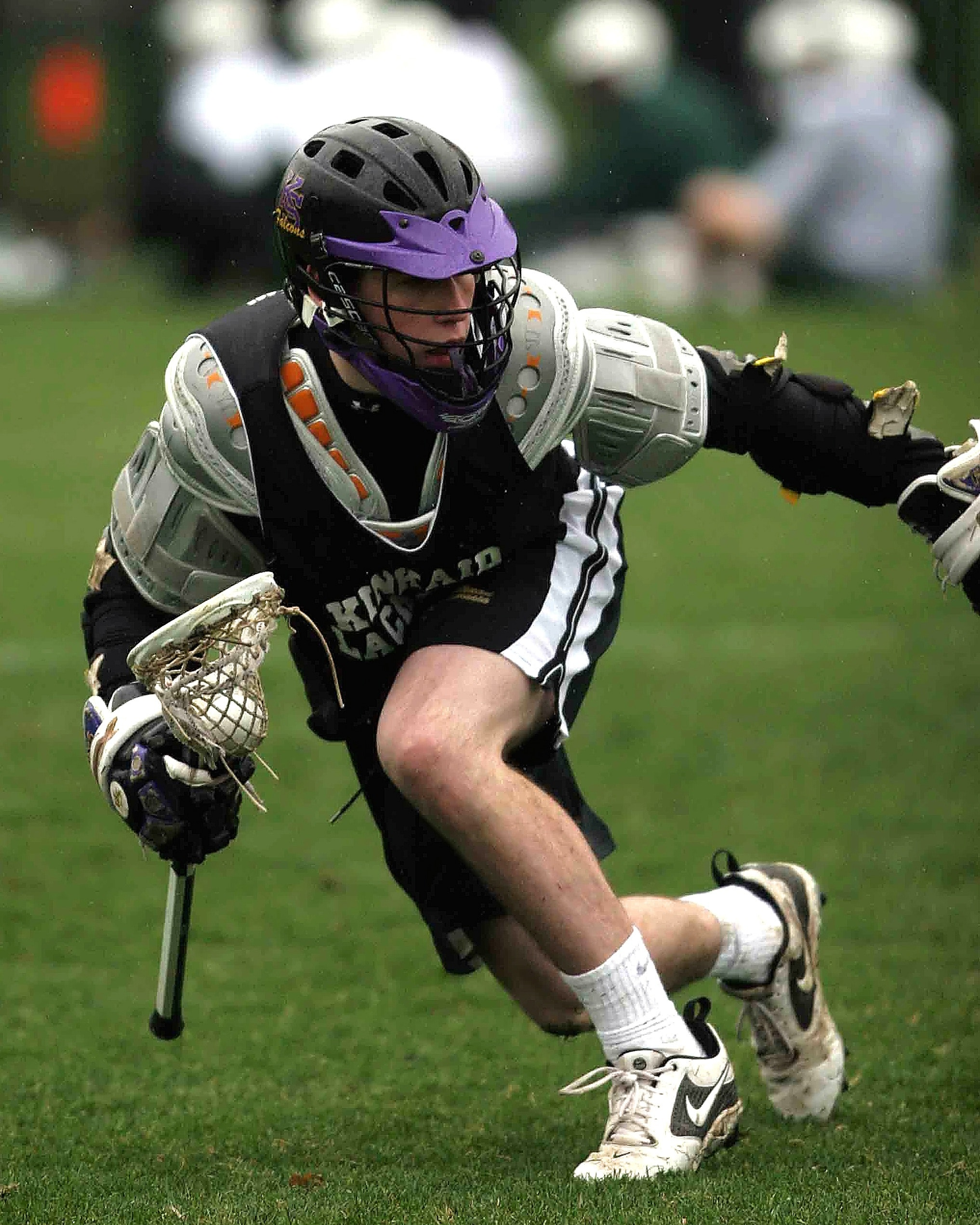 Person in black sports jersey playing lacrosse photo