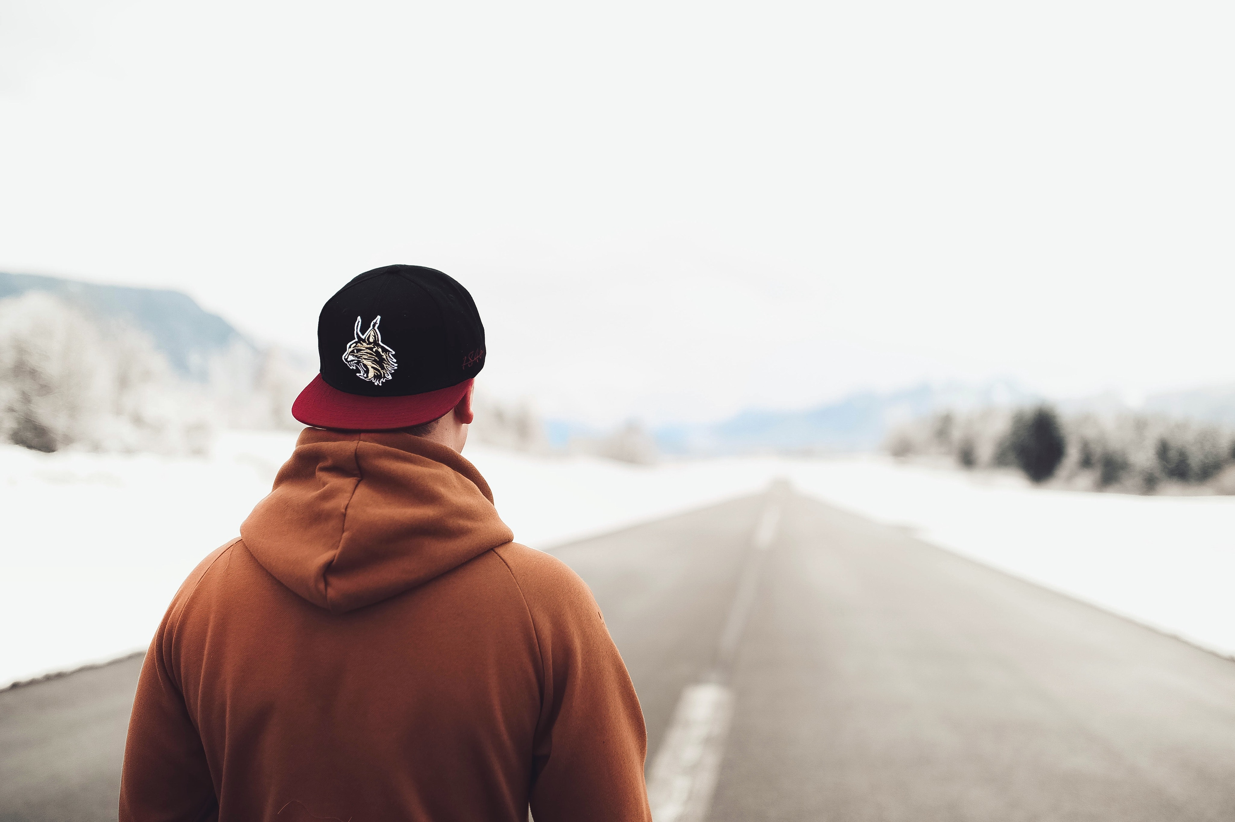 Person in brown hoodie and fitted cap walking on road photo