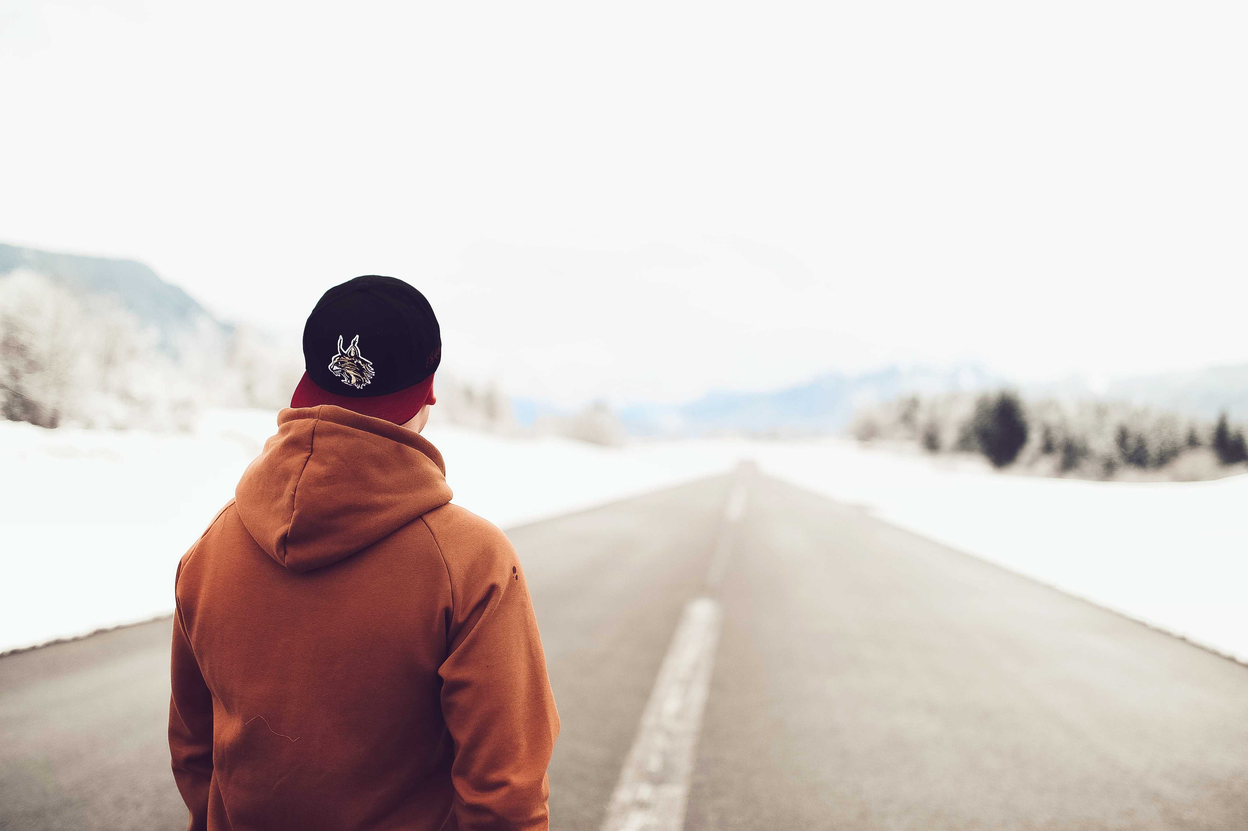 Person in brown hoodie standing on asphalt road photo