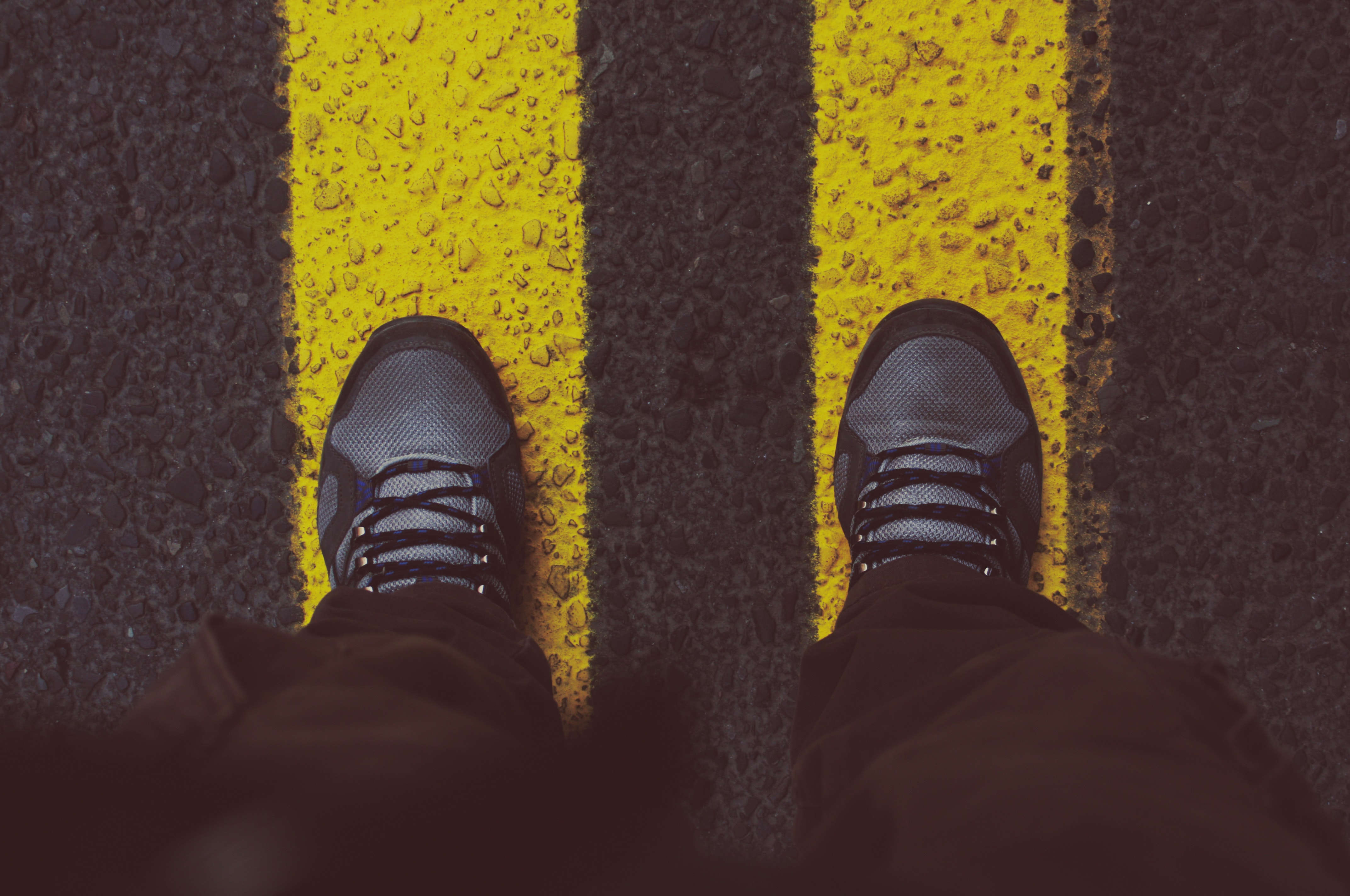 Person in gray sneakers standing on pedestrian lane photo