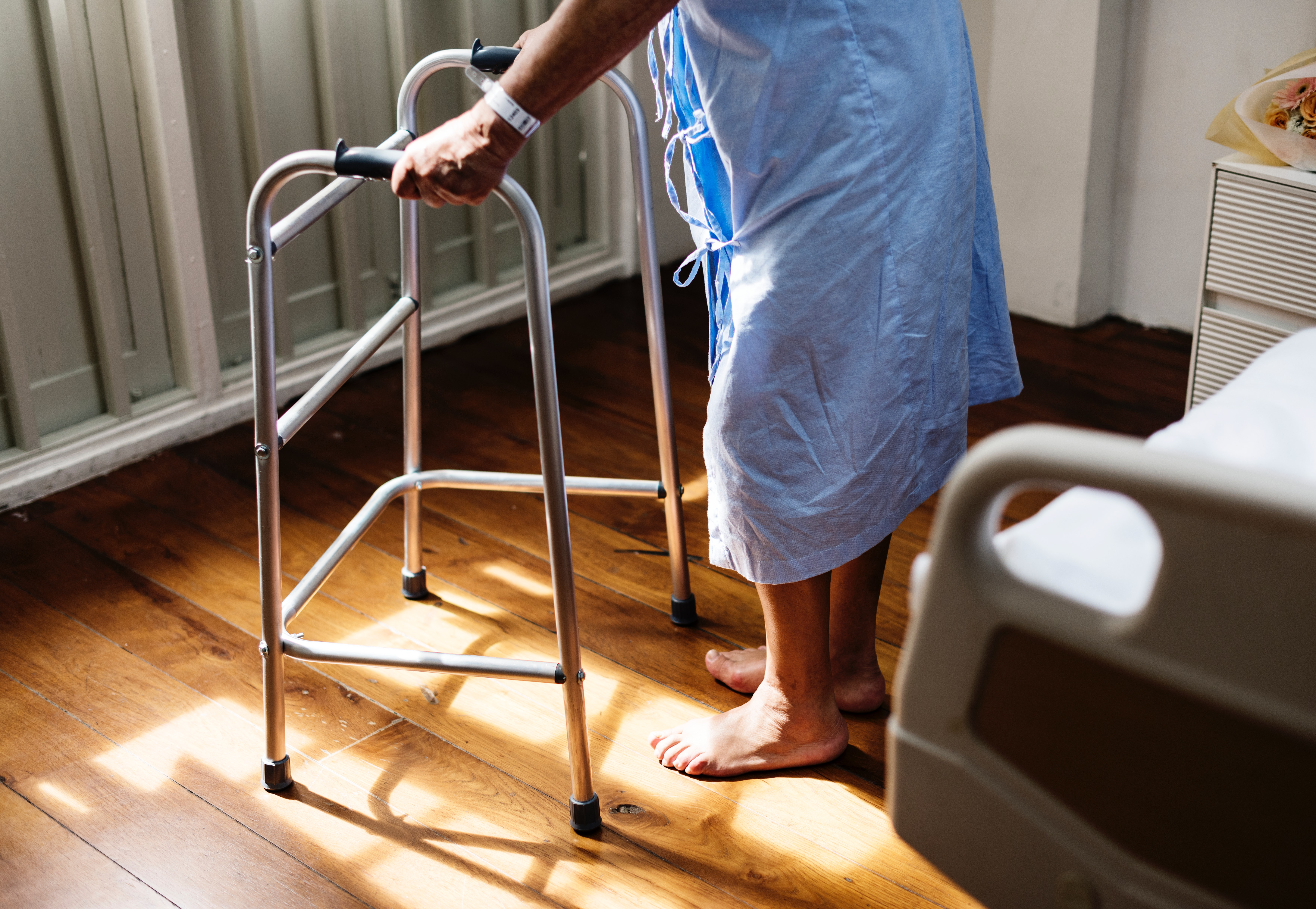 Free photo: Person in Hospital Gown Using Walking Frame Beside ...