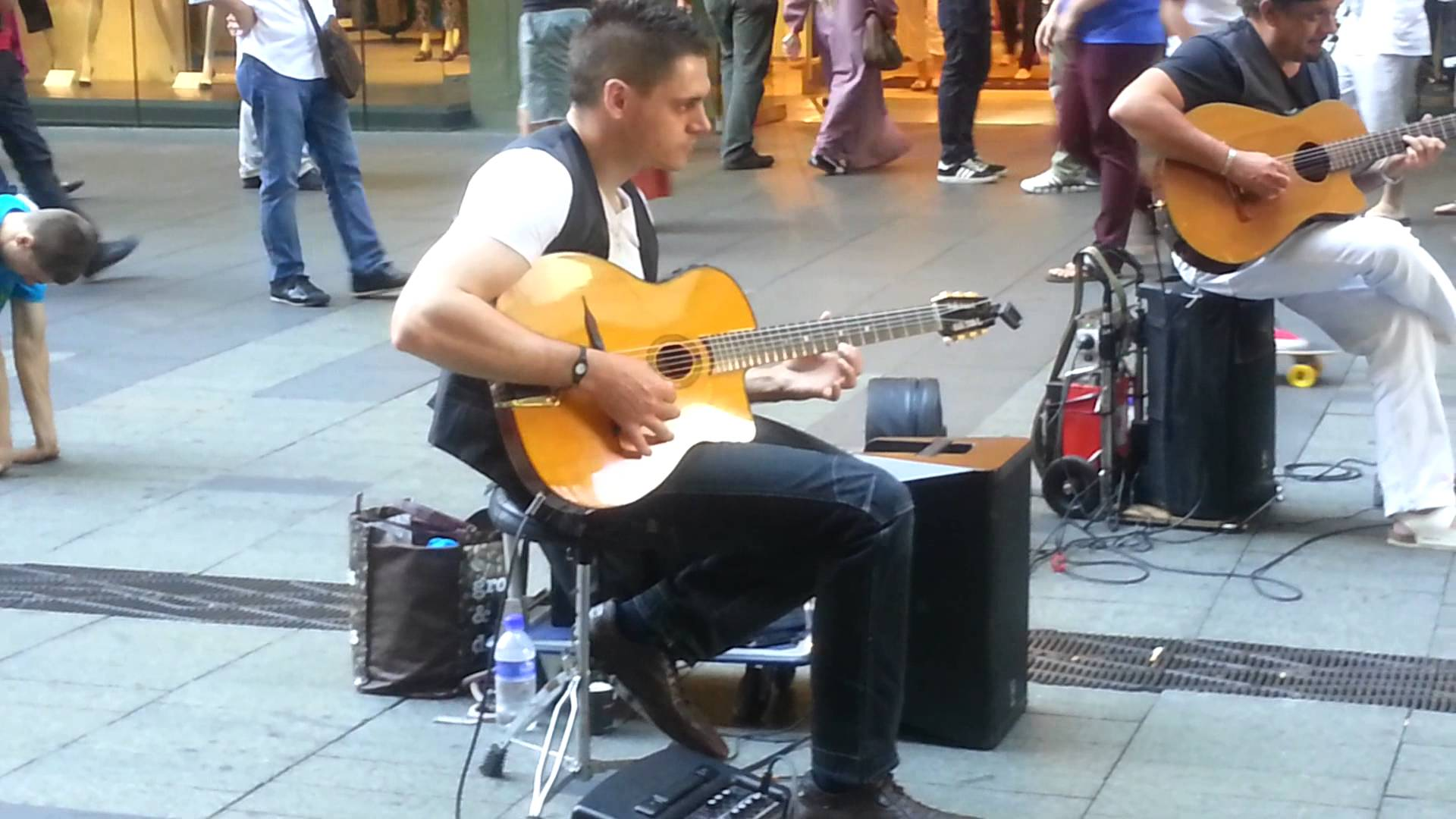 Two Guys Play Acoustic Guitar on the street but their fingers are ...