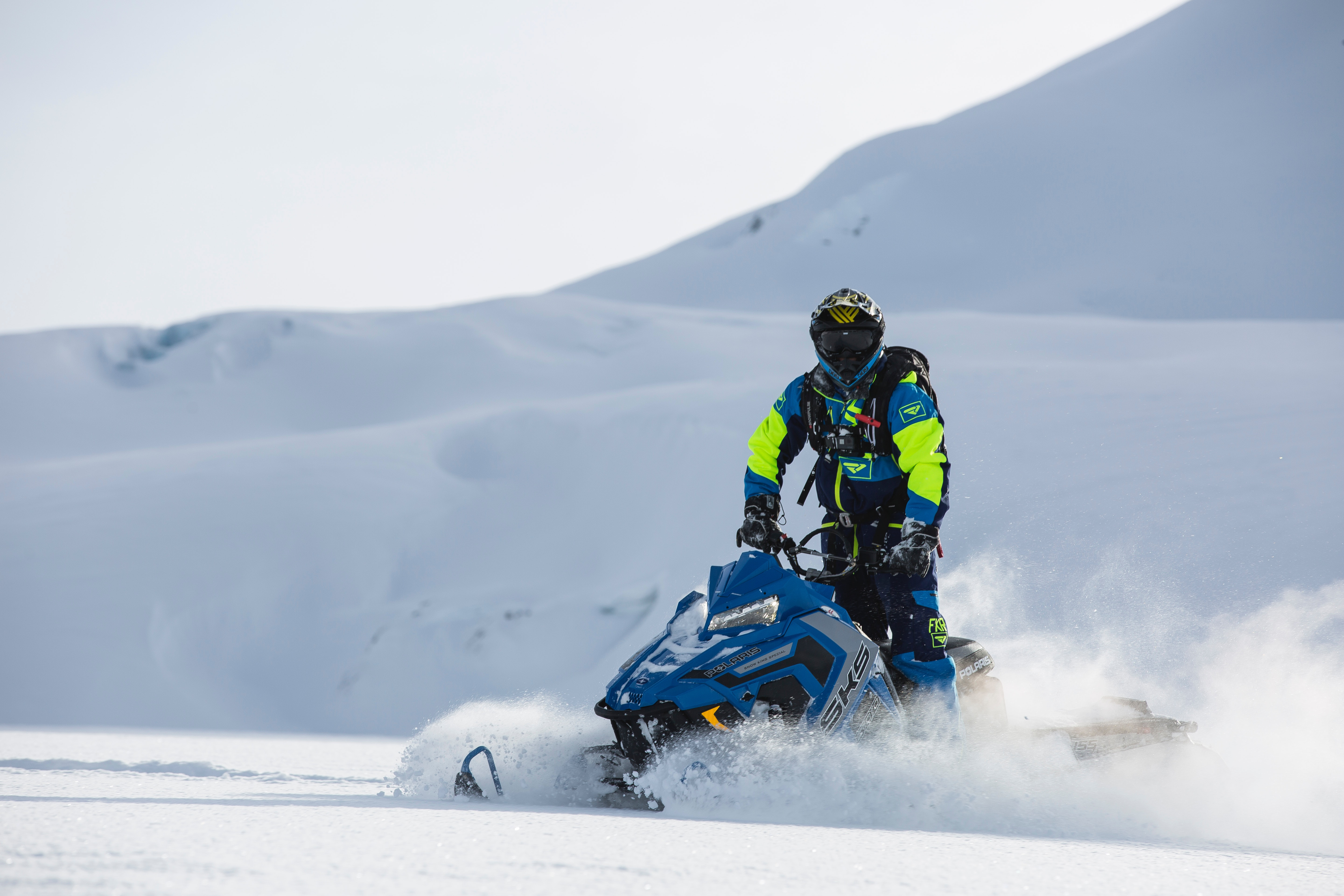 Person rides on blue snowmobile at daytime photo