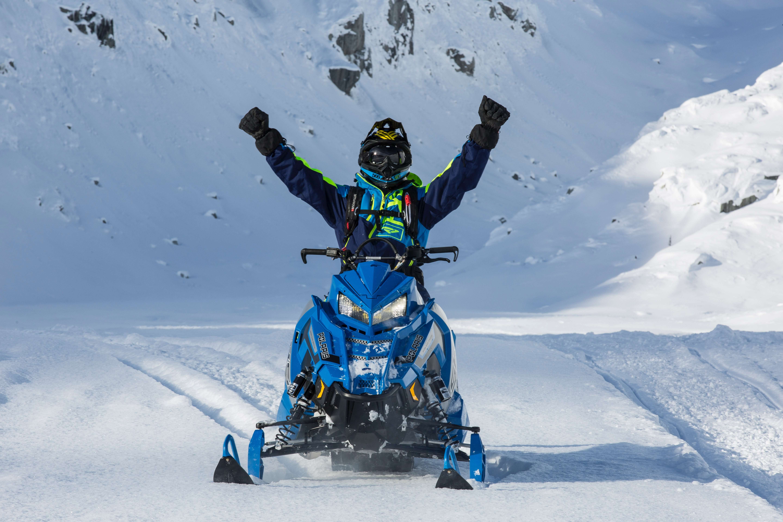 Person riding blue snow mobile photo
