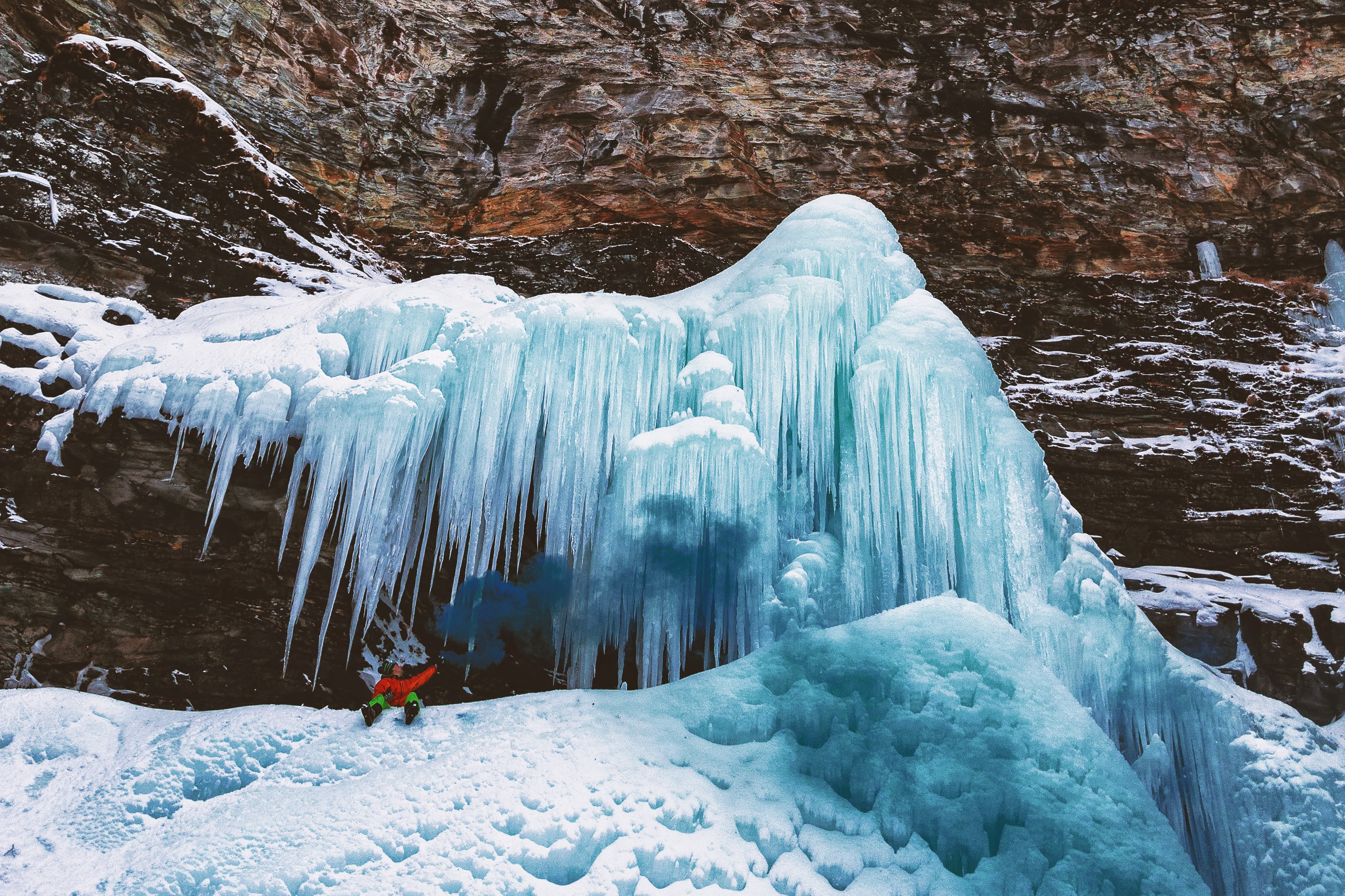 Person sits on mountain with icicles photo