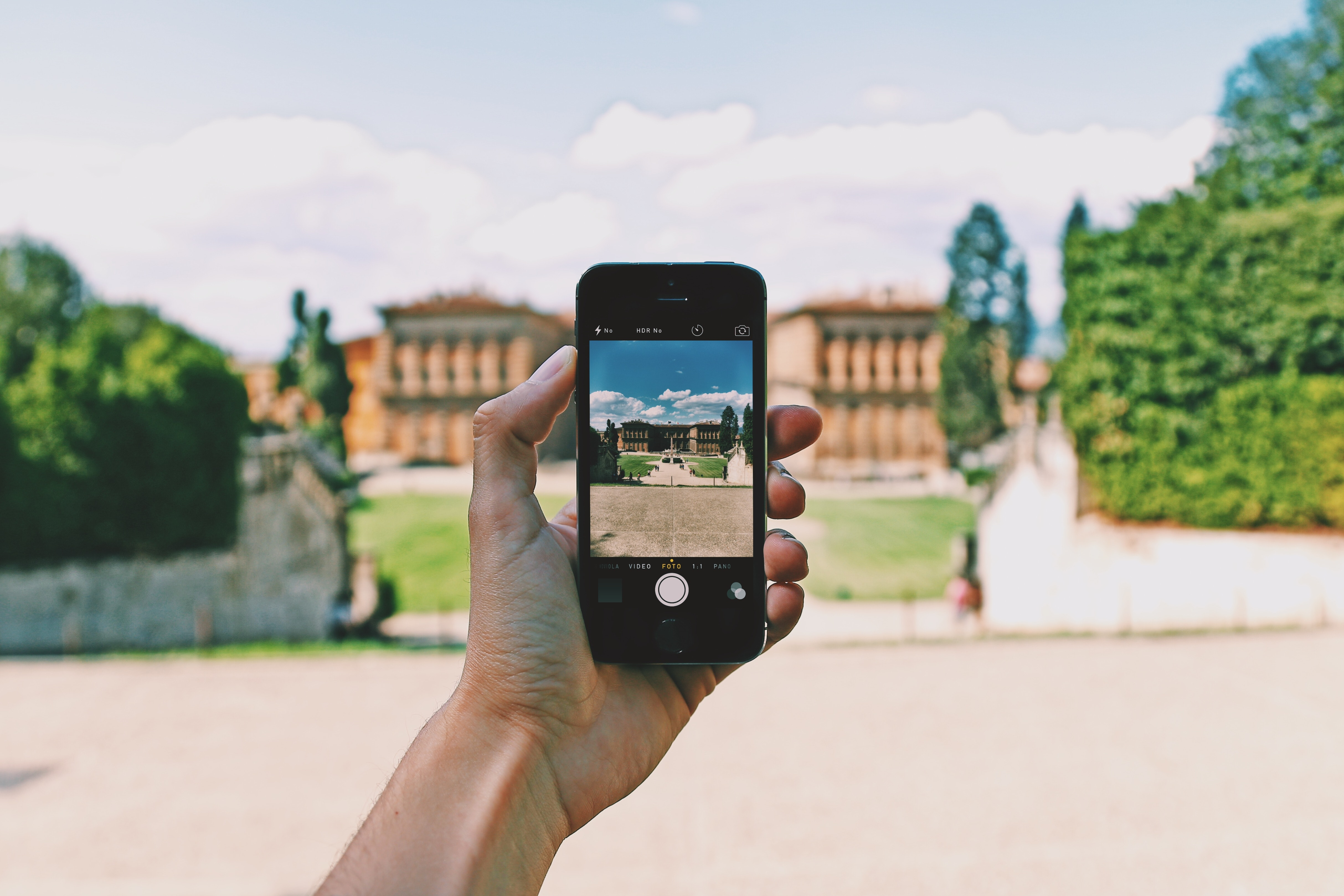 Person using space gray iphone 5s taking a picture of landmark during day photo