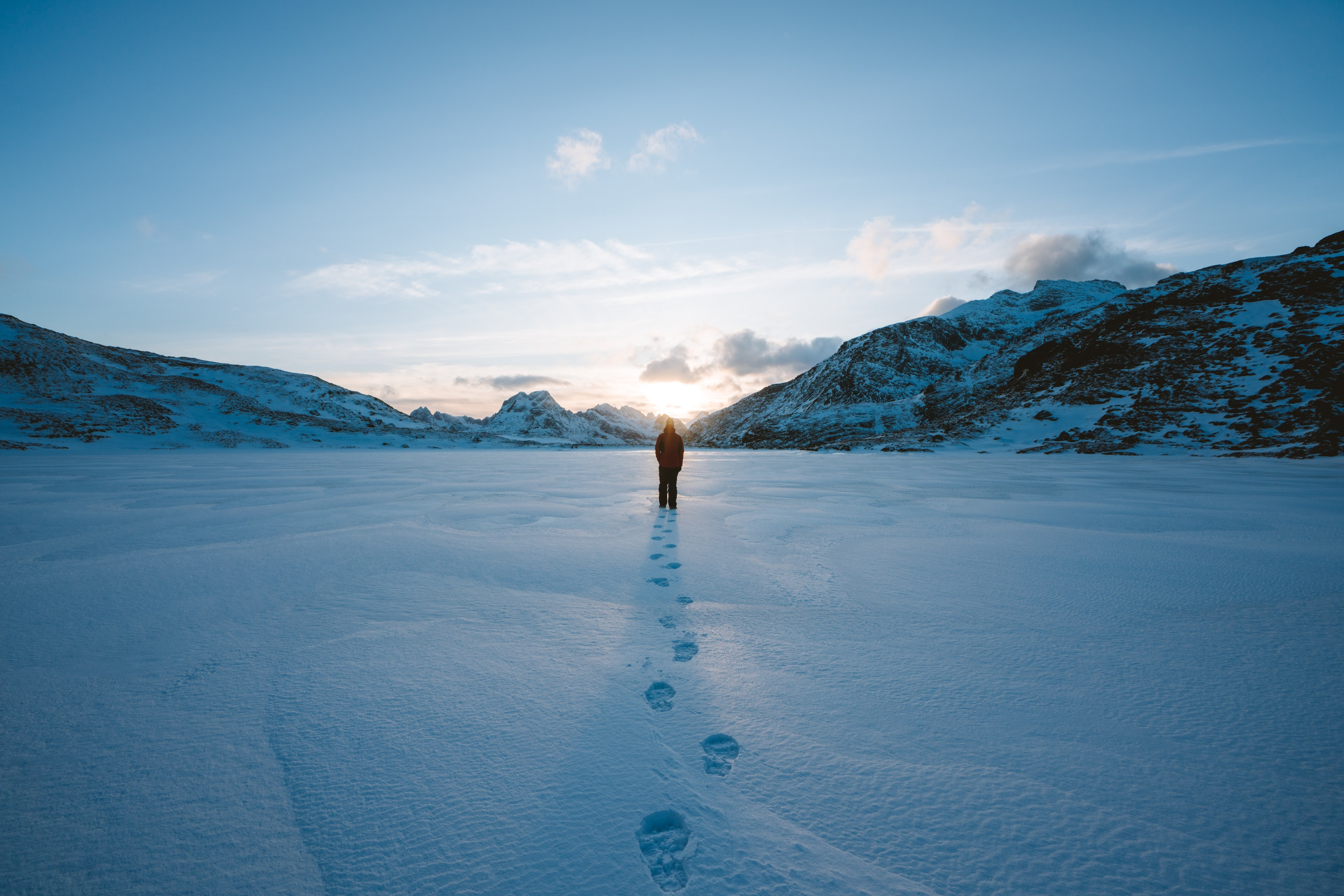 Person walking in snow field near mountain cliff covered with snow photo