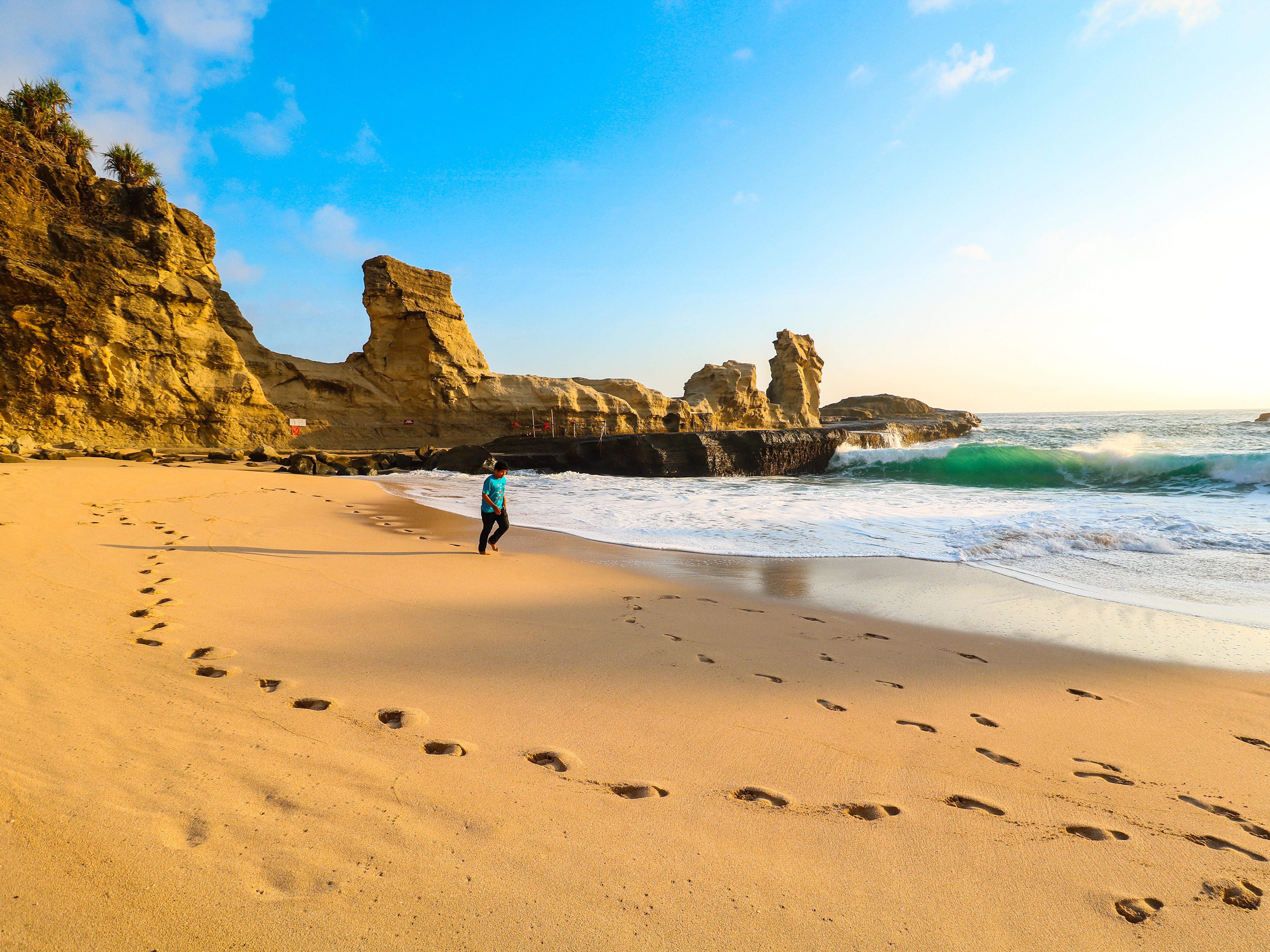 Person Walks on Brown Seashore Near Rock Formations, Beach, Scenery, Water, Sunshine, HQ Photo